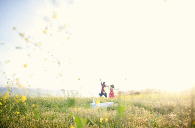 couple jumping on bed in field