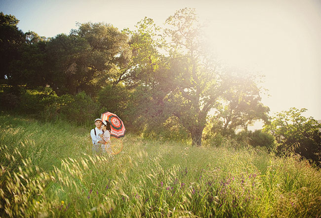 couple with umbrella in field engagement photos
