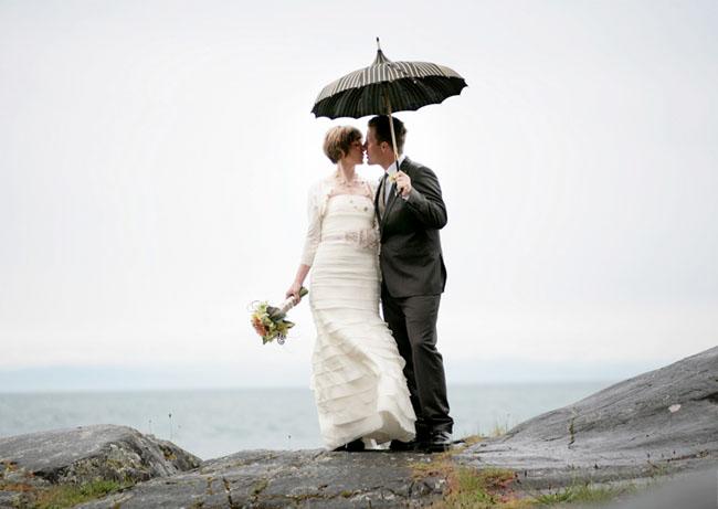 rainy wedding couple with vintage parasol umbrella