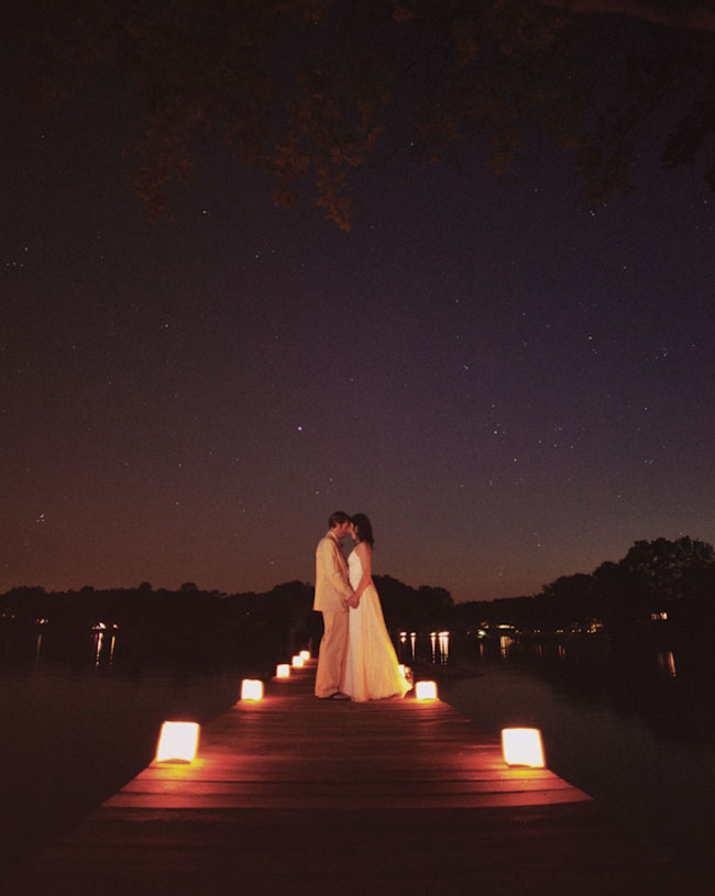 bride and groom on a pier at night