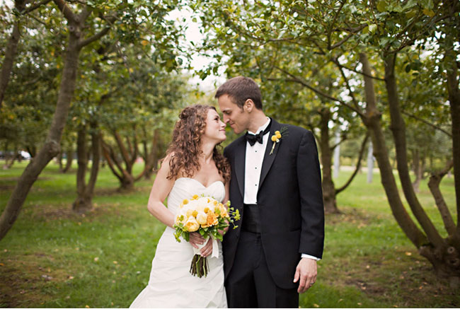 bride and groom with bouquet in orchard