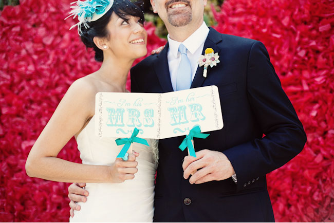 bride and groom with mr. and mrs. signs