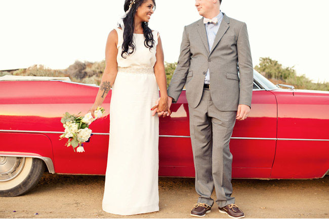 bride and groom with red car