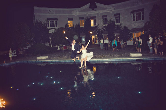 bride and groom jumping in pool