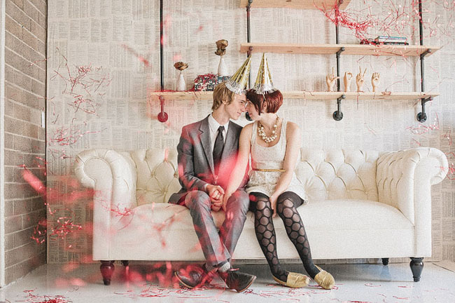 couple in new years hats, white sofa