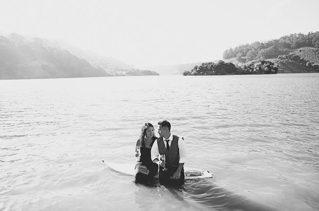 couple on surfboard with wine