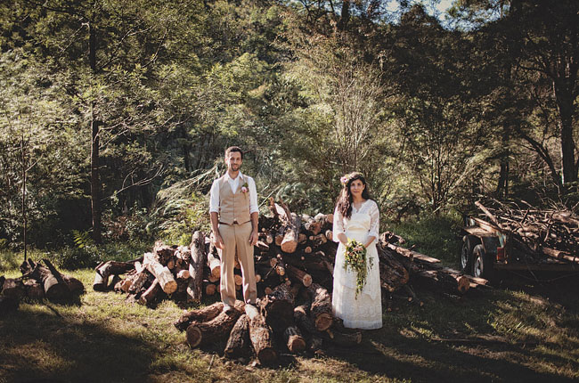 wedding couple by pile of wood