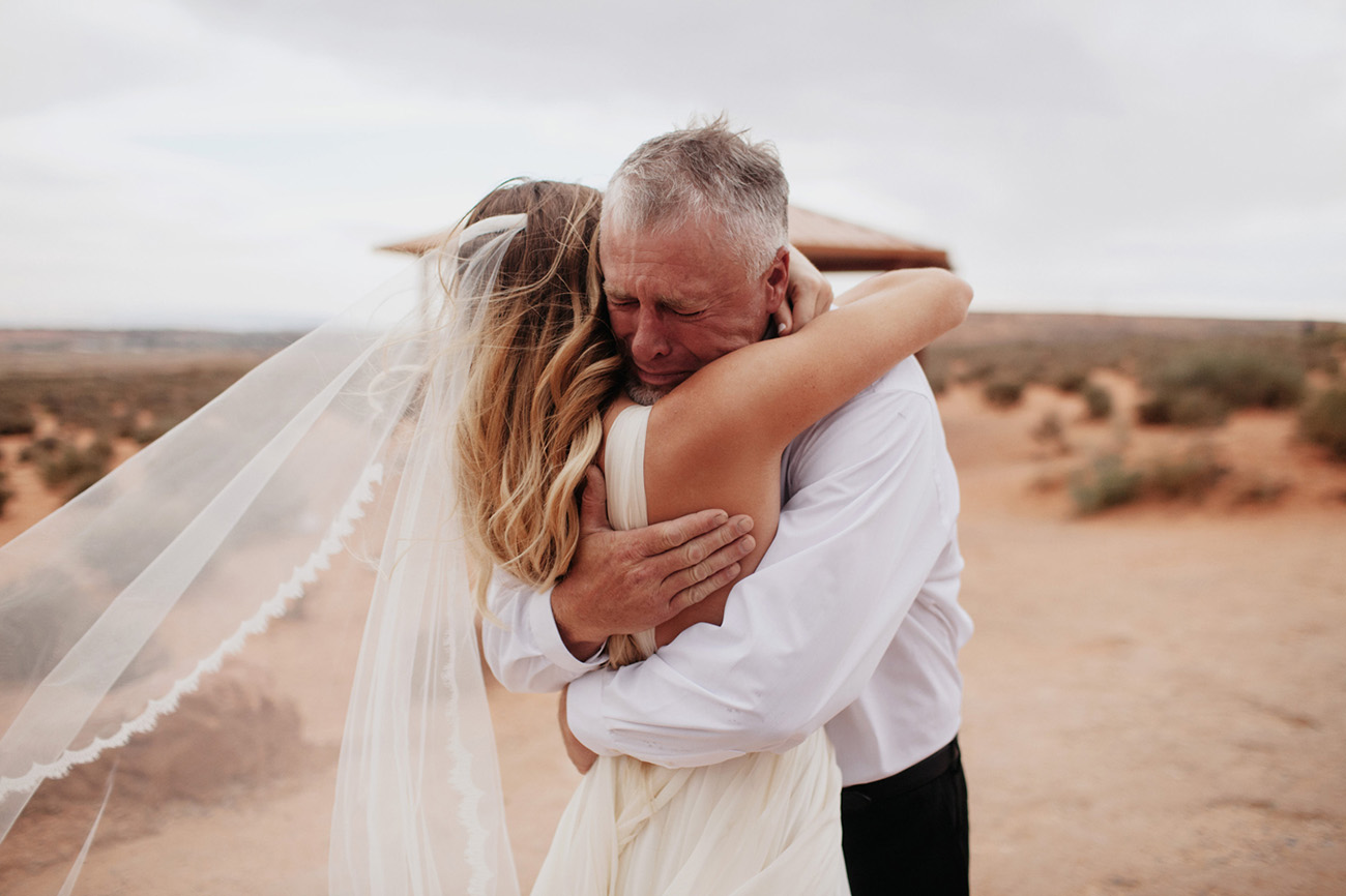 bride with dad after seeing her in wedding dress