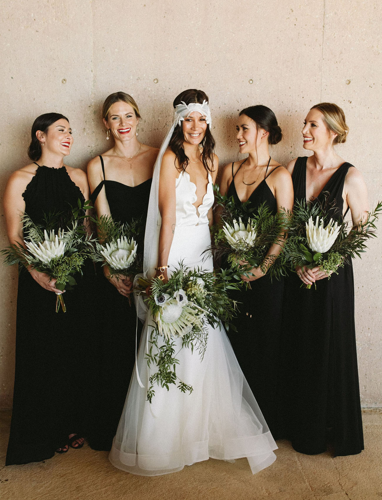 black bridesmaid dresses with protea bouquets