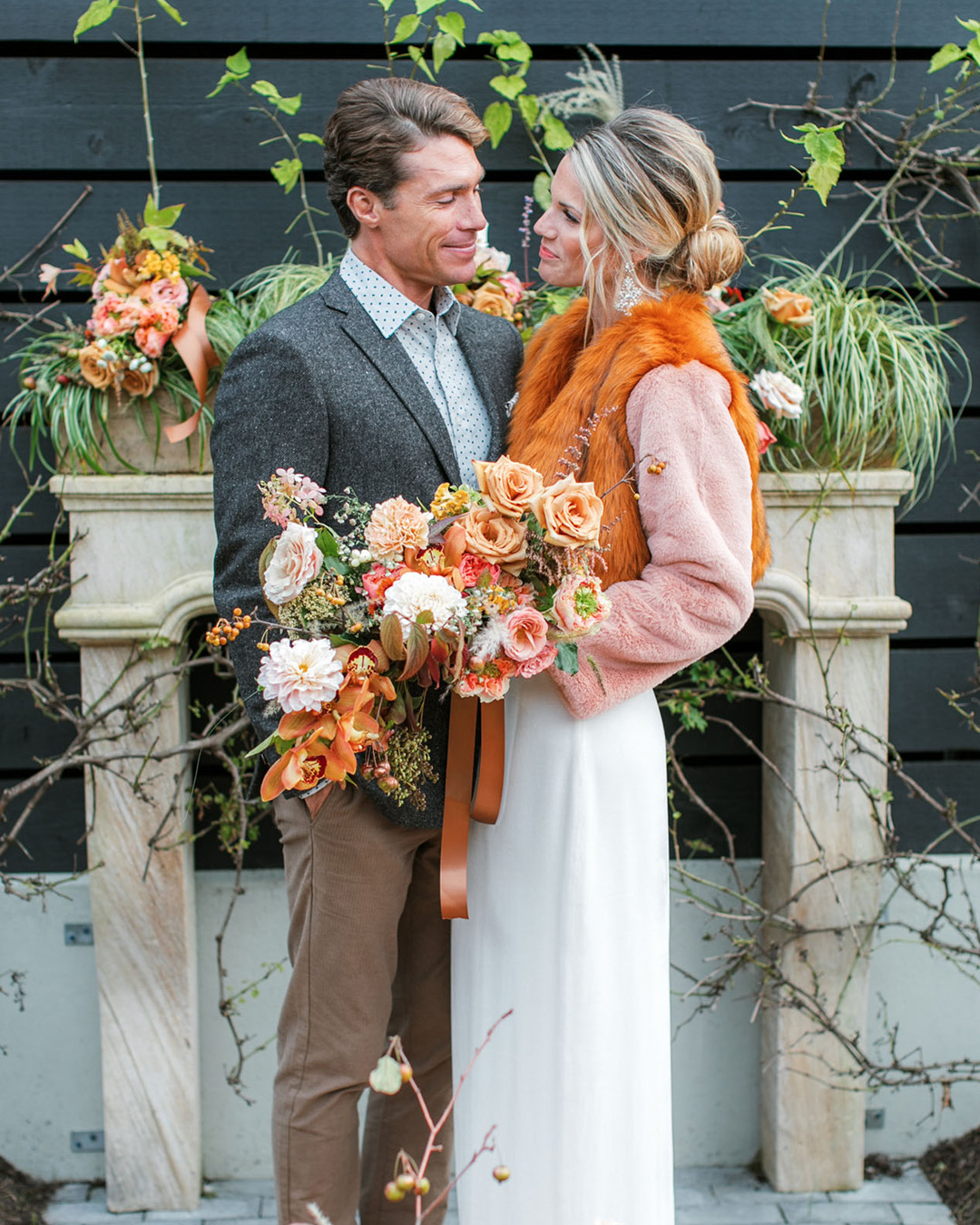bride wearing a orange faux fur jacket