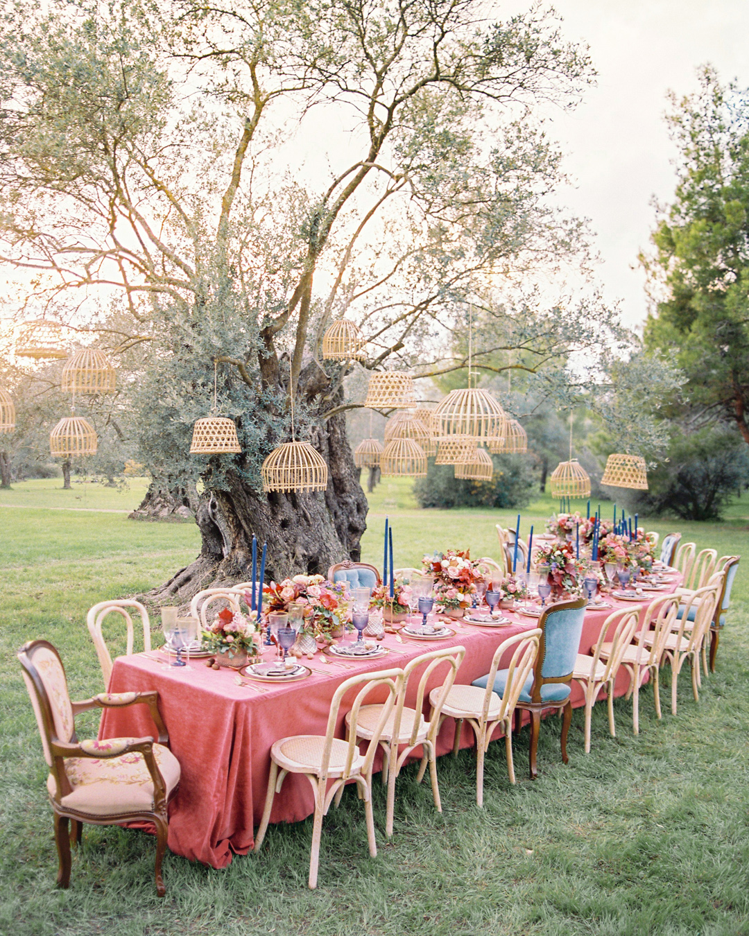 family style table with hanging lanterns in a tree