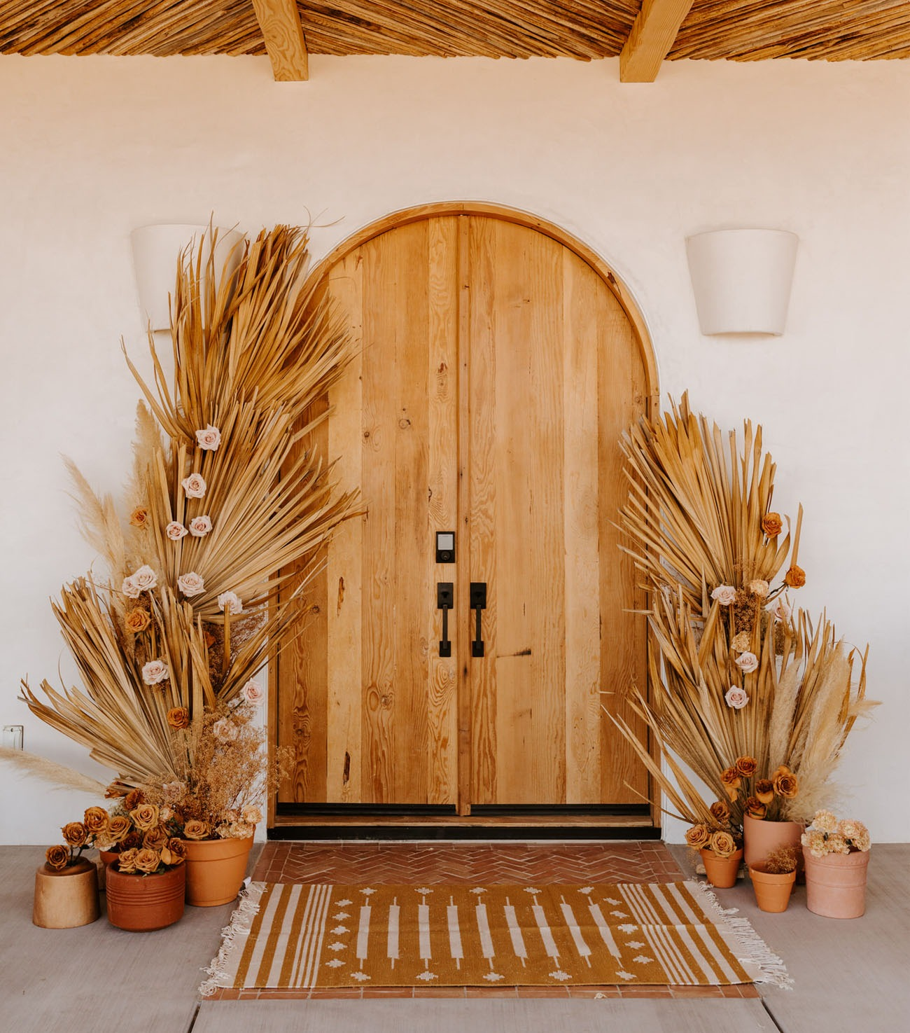 dried grass decorating an arched doorway being used as a DIY wedding backdrop