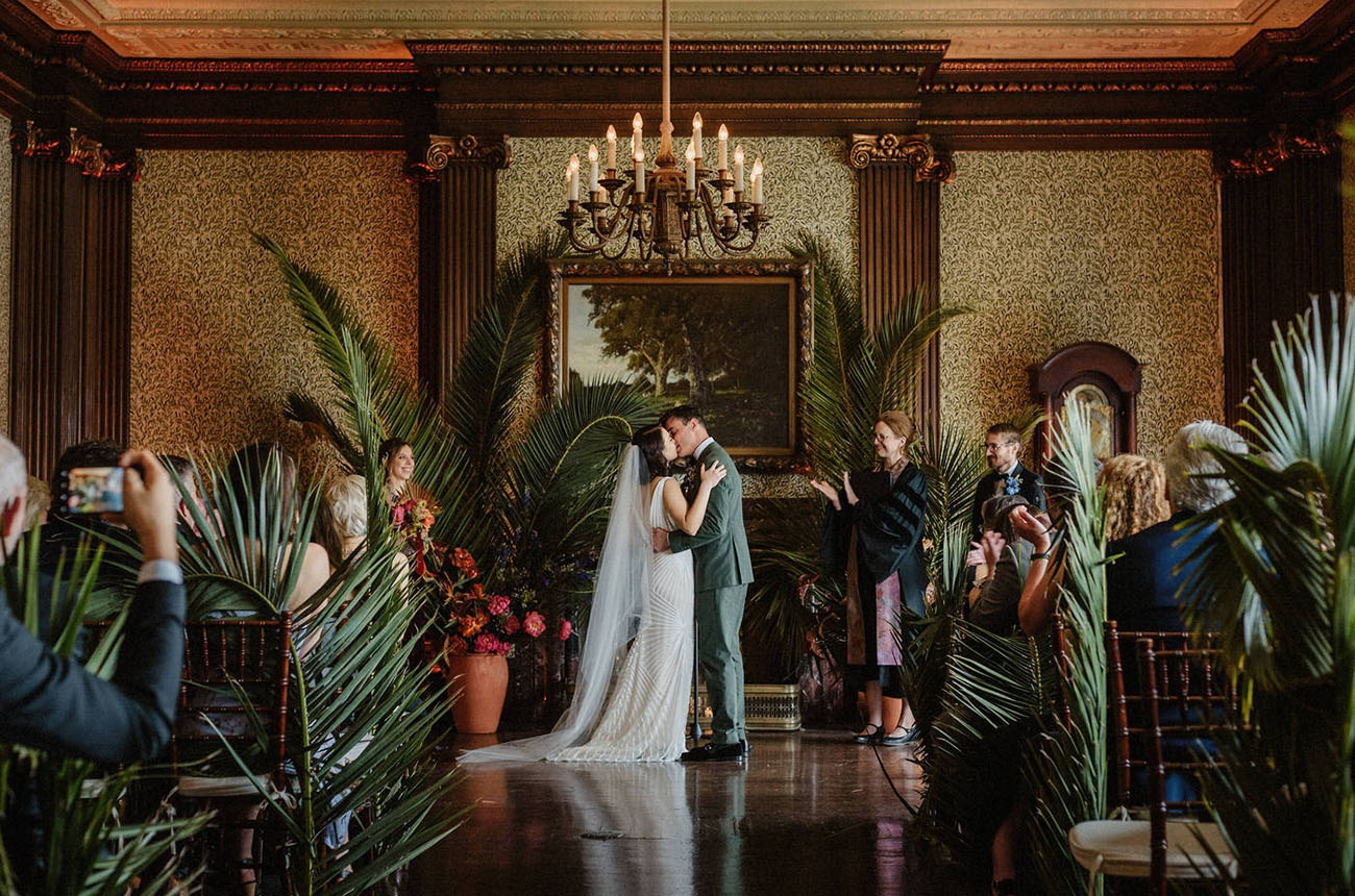 plants framing a fireplace and painting being used as a DIY wedding backdrop