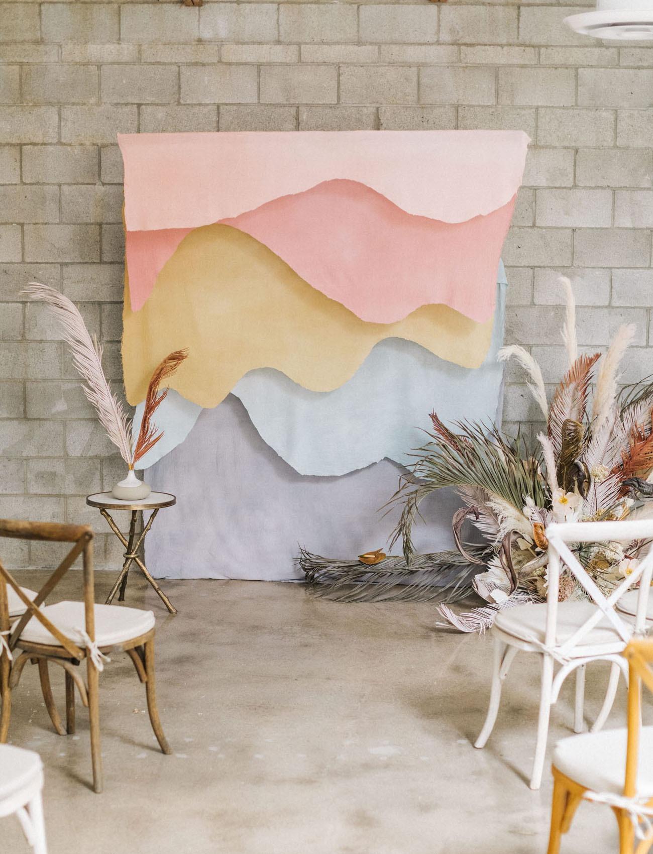 pastel cloth waves DIY wedding backdrop at an indoors industrial wedding venue