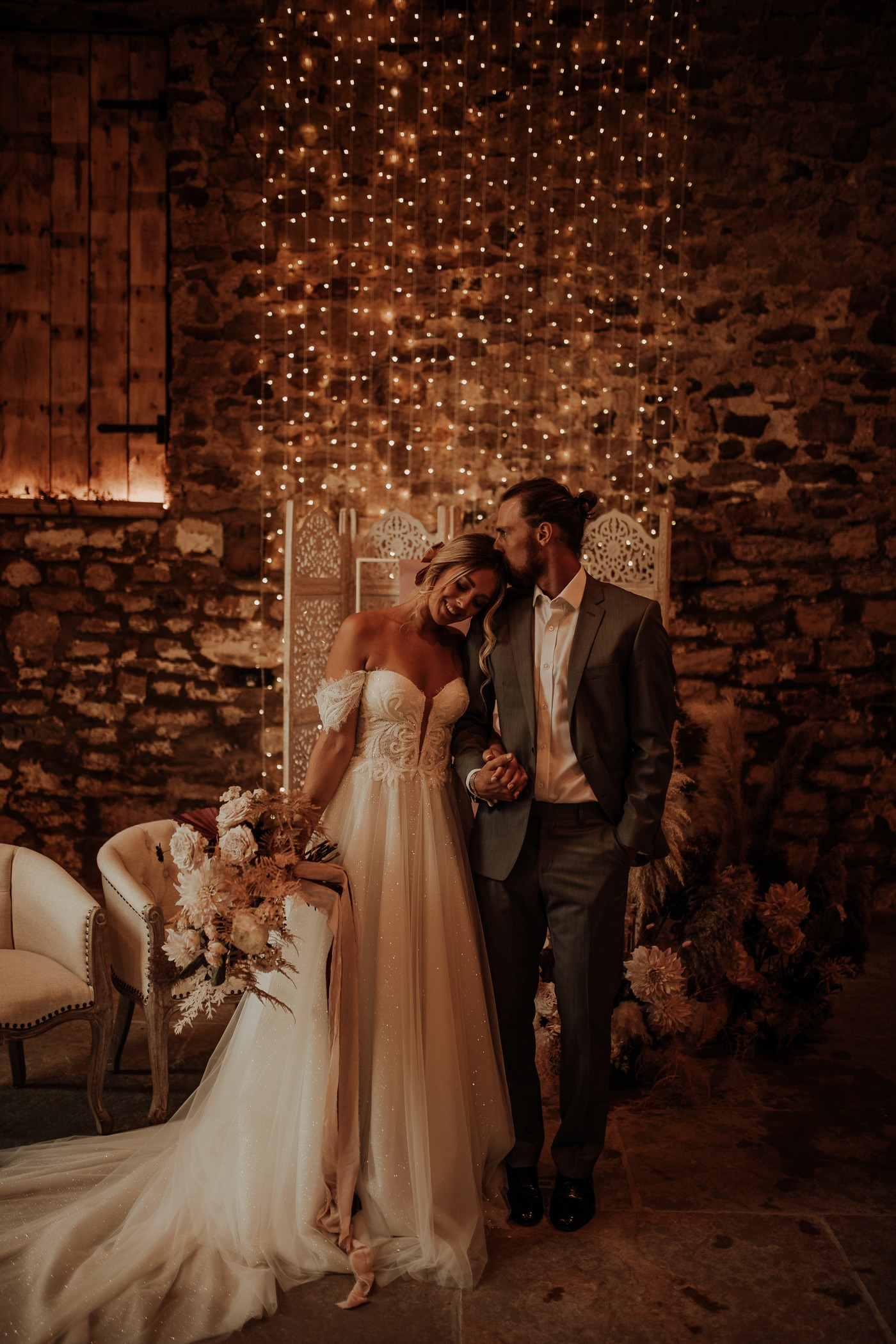 couple standing in front of a fairy twinkle lights DIY wedding backdrop in a dimly lit venue