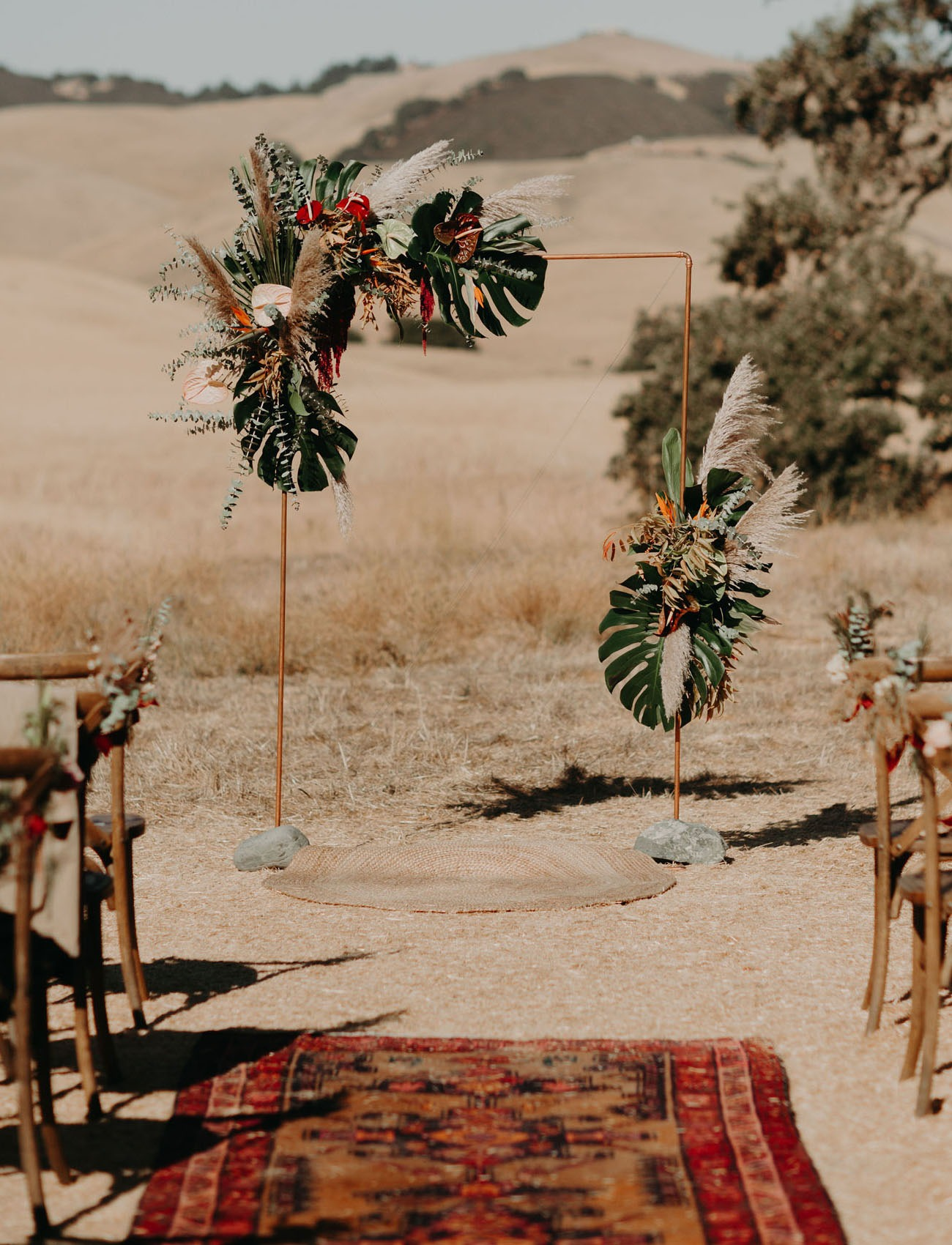 copper pipe wedding backdrop arbor with tropical plants