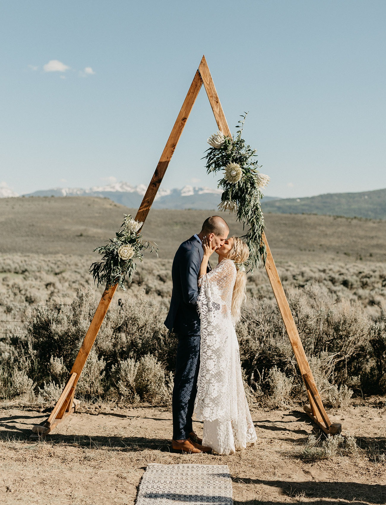 wooden triangle wedding backdrop in the mountains