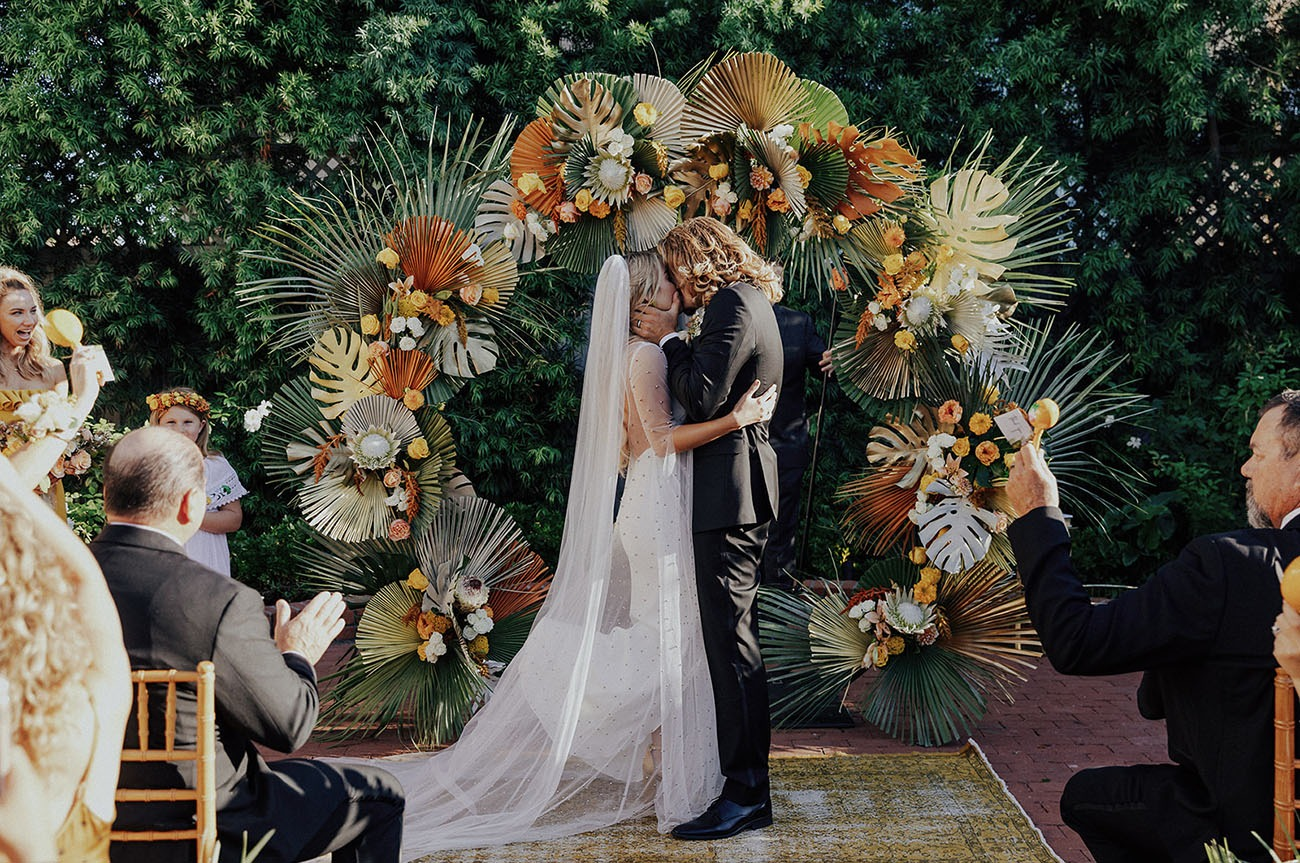 couple kissing in front of a tropical circular wedding backdrop