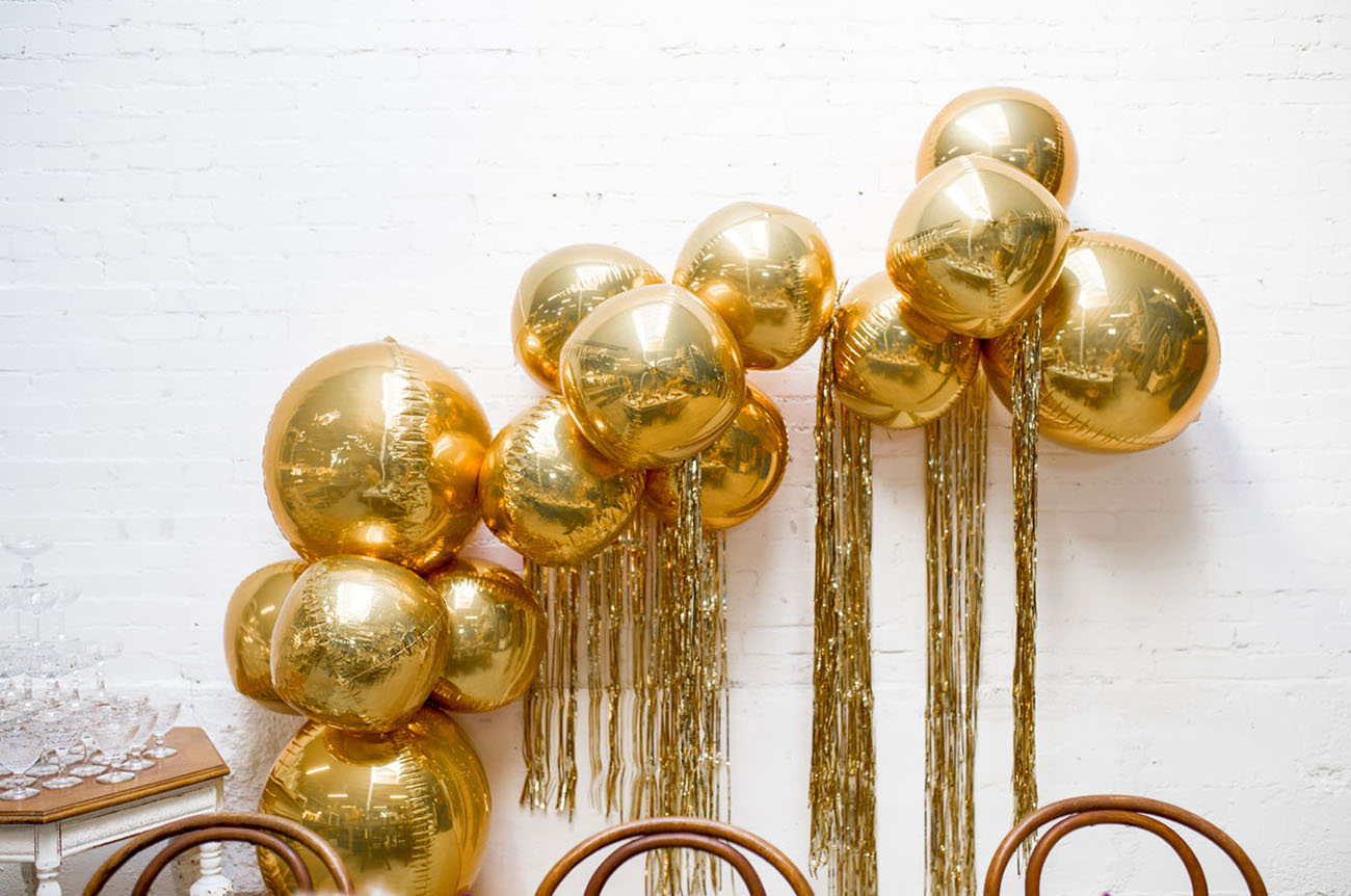 gold fringe balloon arch