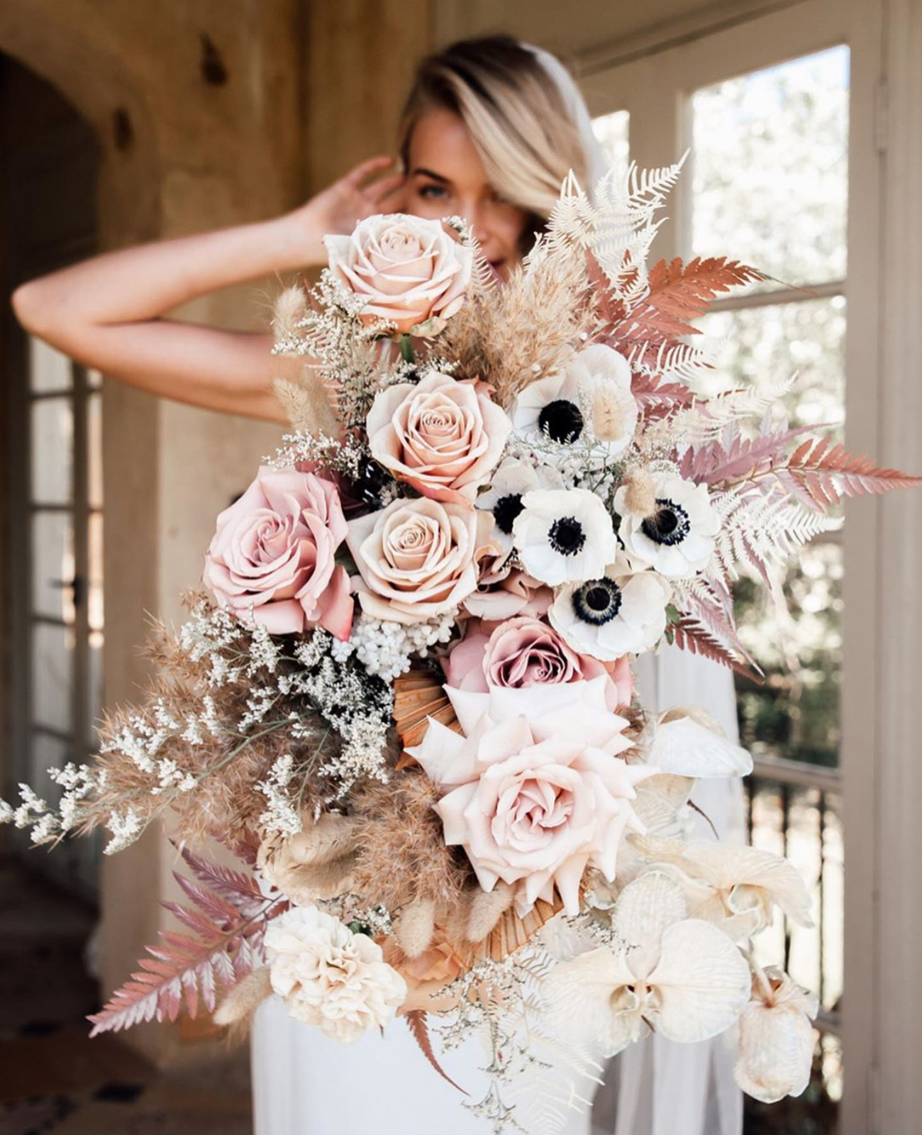 winter bouquet with anemones, pink roses, and gold ferns