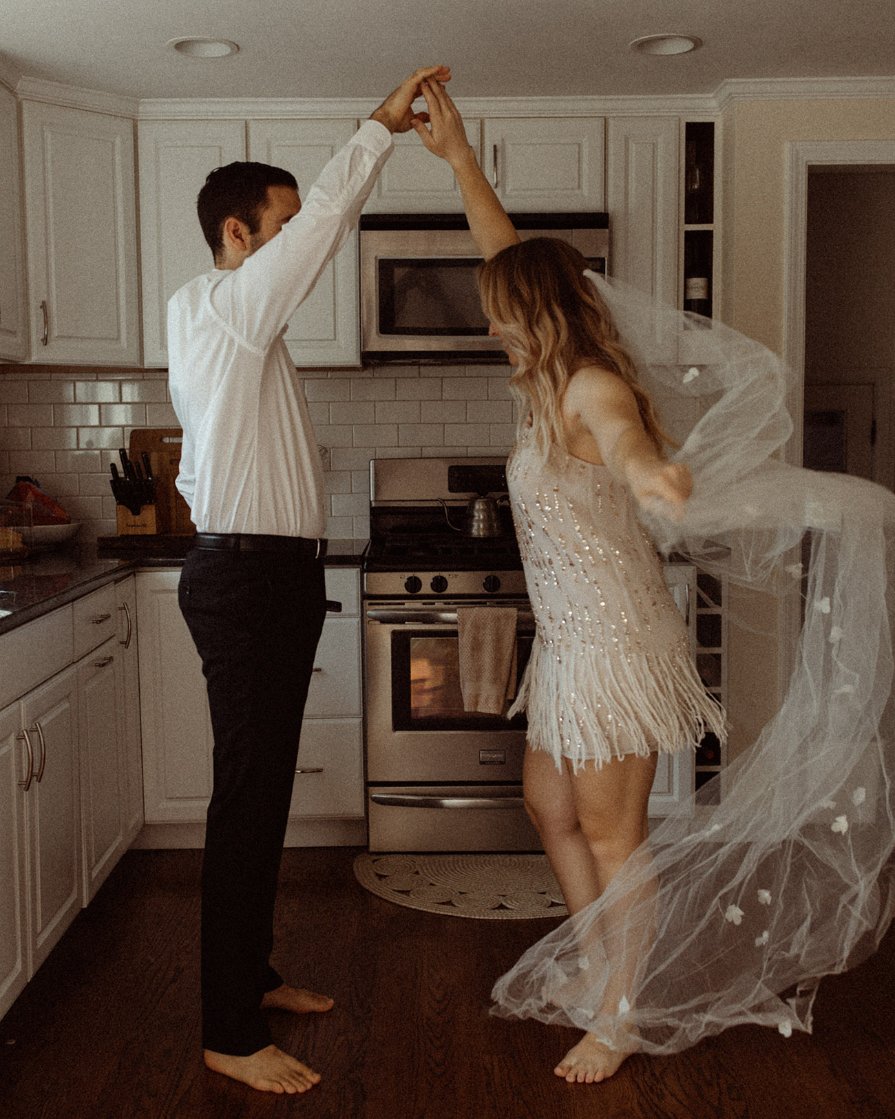bride and groom dancing in their kitchen