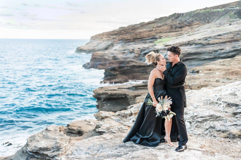 couple in black wedding attire on cliffs