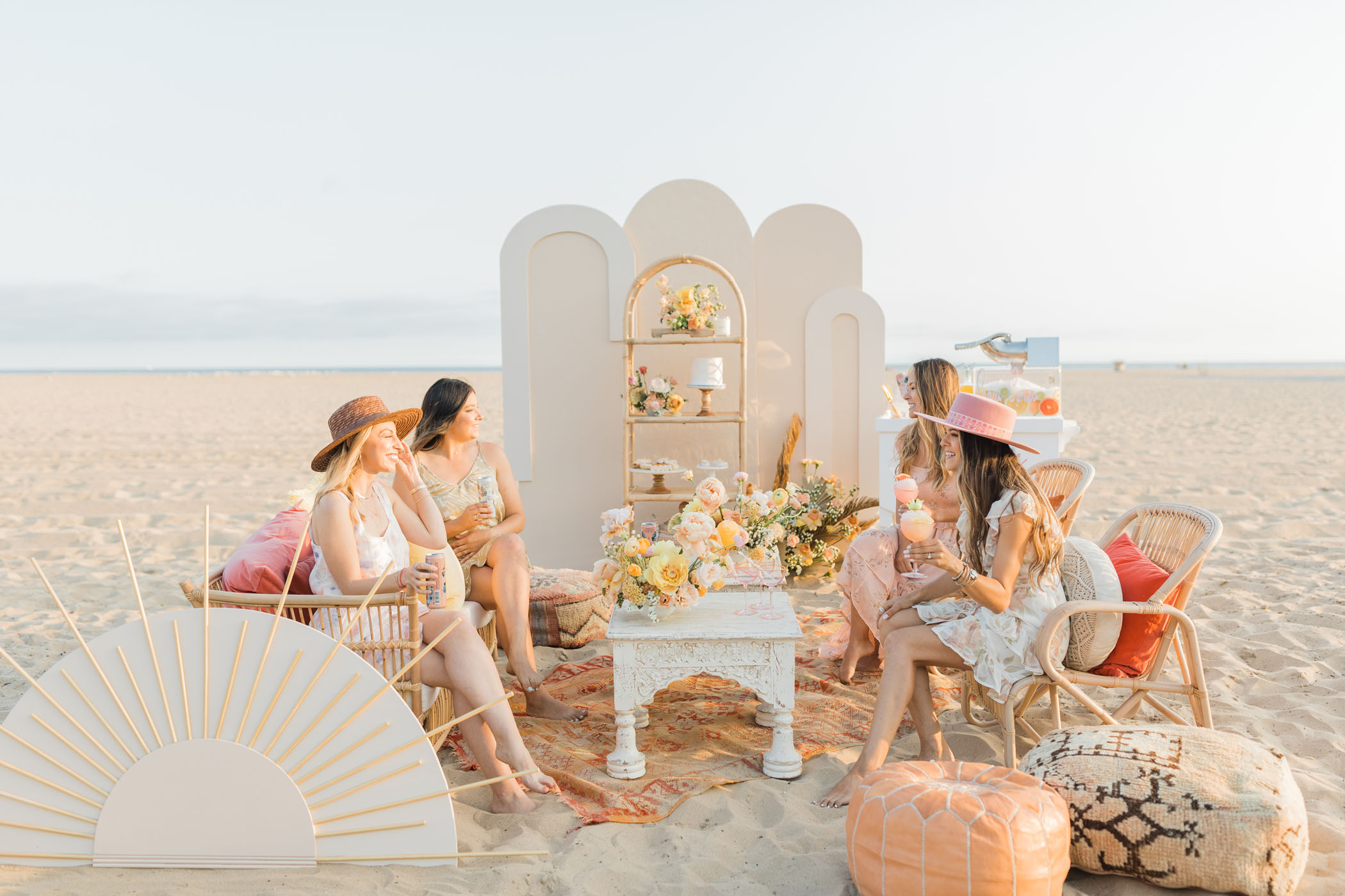 bridesmaids sitting in the lounge area of a beach themed bridal shower with colorful pastel decorations