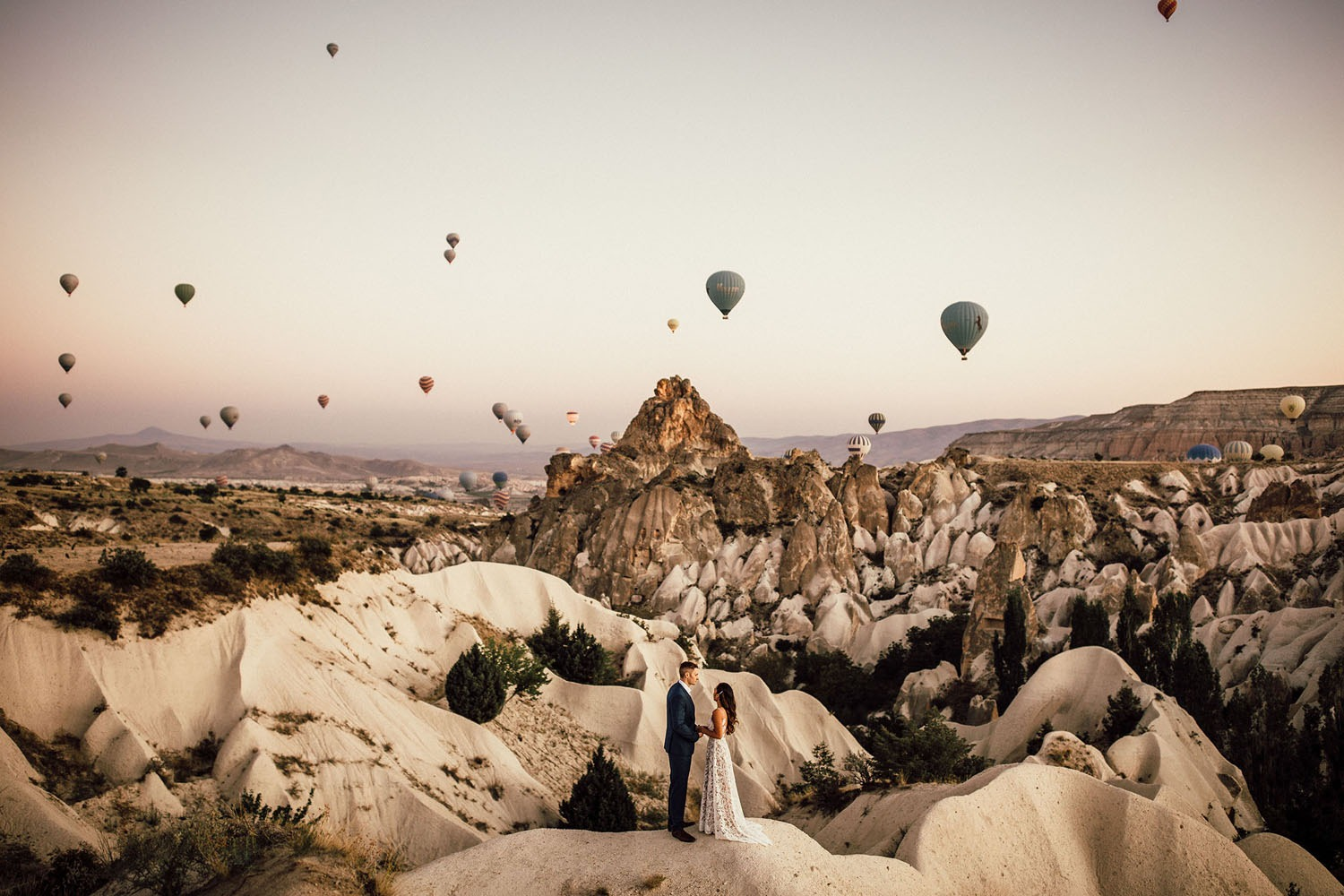 couple getting married with hot air balloons rising behind them in Cappadocia Turkey