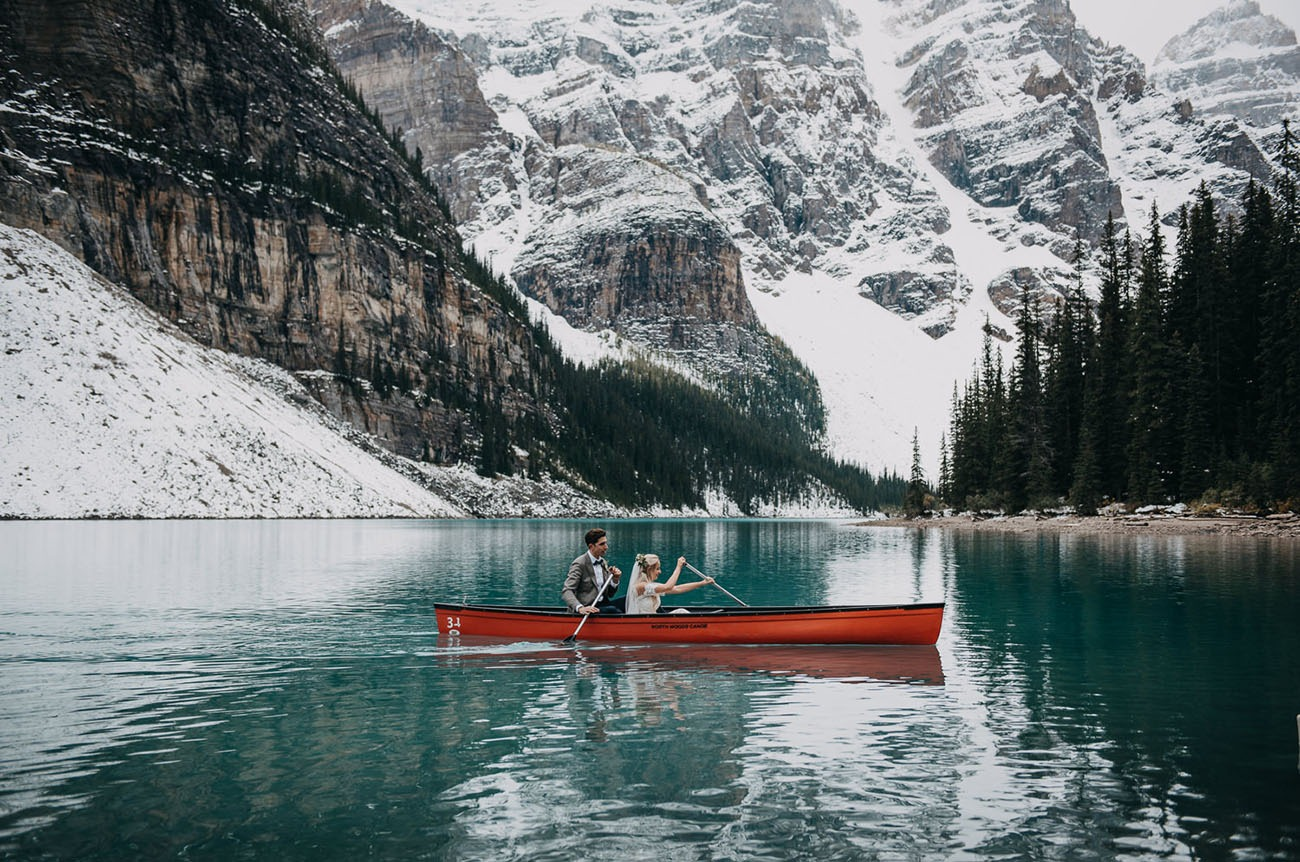 couple paddling in a red canoe on Moraine Lake in Banff National Park in Alberta Canada for their destination wedding