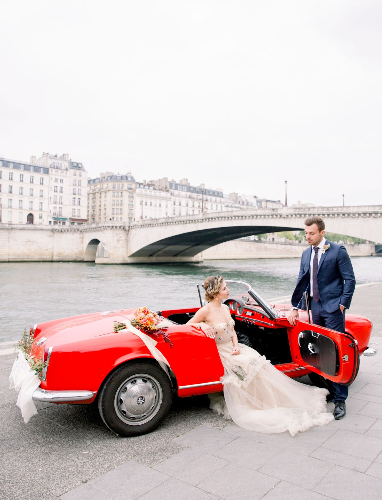 couple sitting in a vintage red car by the Seine in Paris on their wedding day