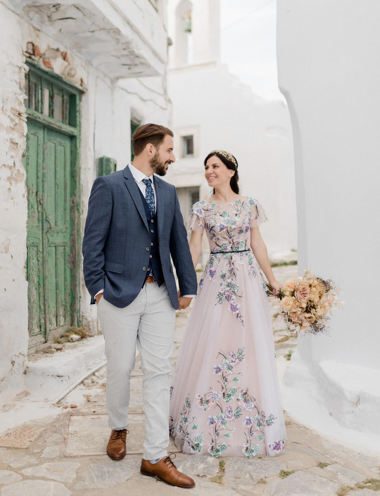 couple wandering the streets of Santorini Greece during their destination wedding
