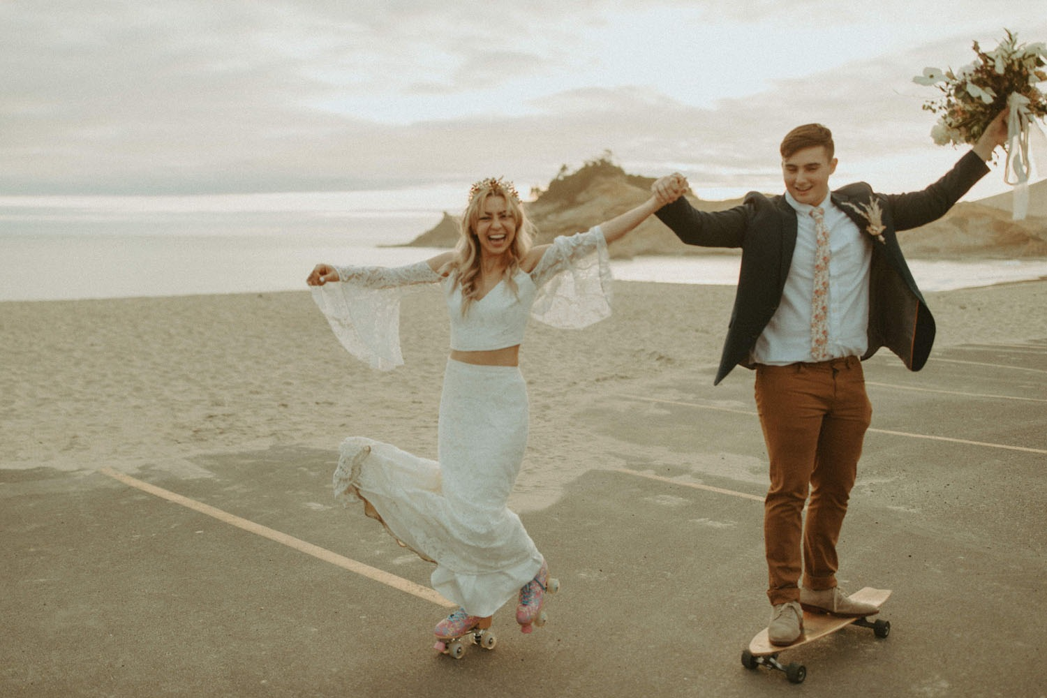 couple roller blading and skateboarding by the beach during their Cape Kiwanda destination wedding