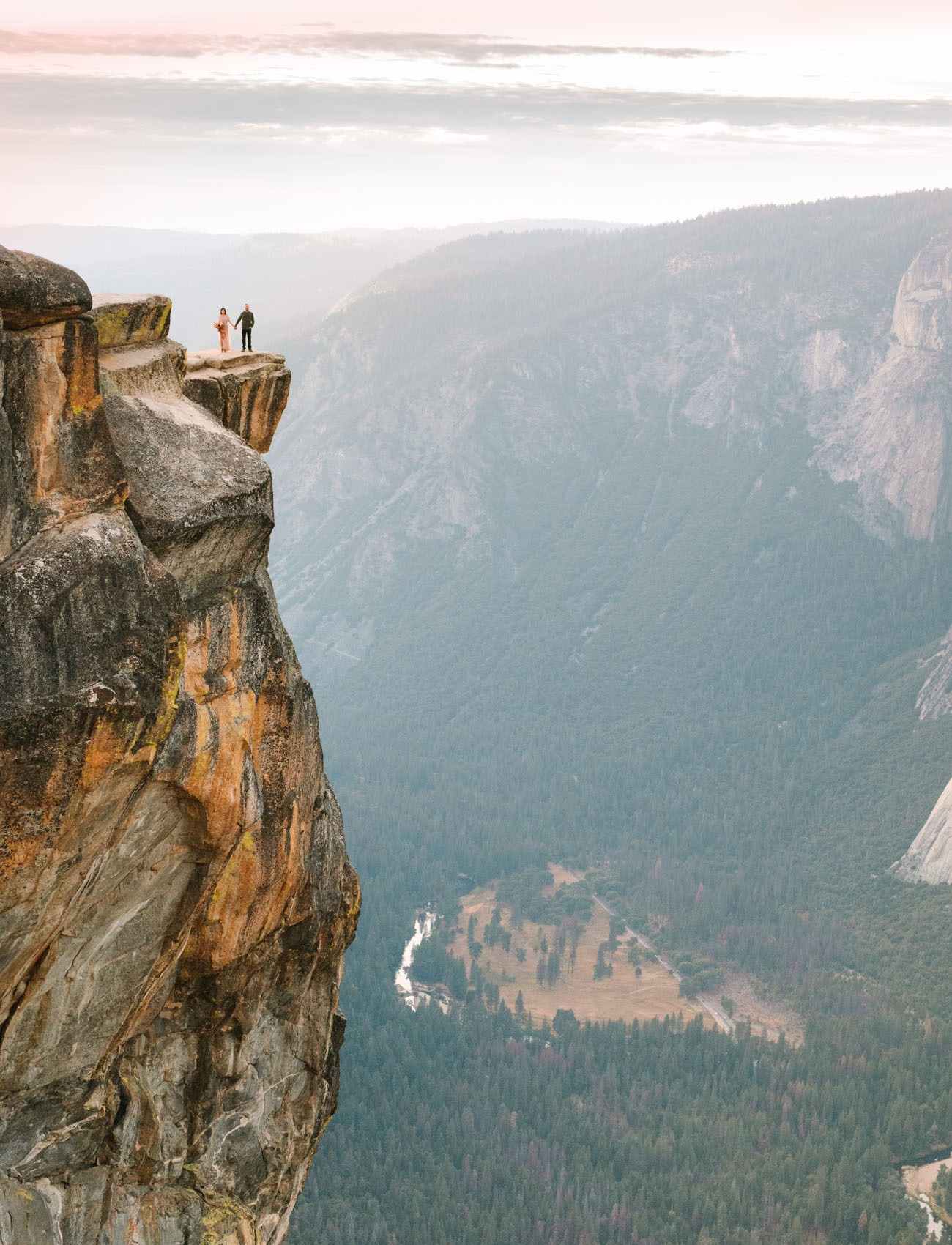 couple standing on the edge of a cliff in Yosemite, an epic honeymoon destination
