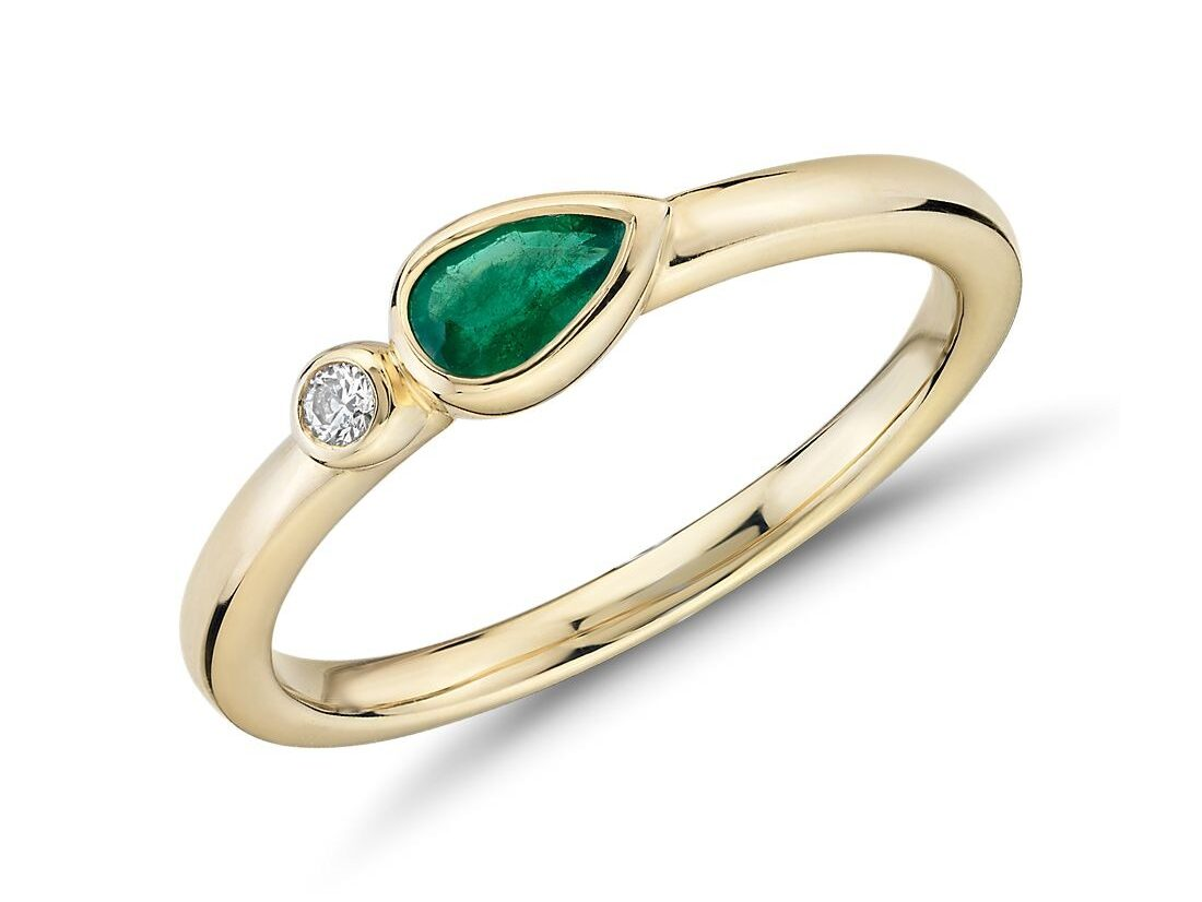bezel set tilted pear shaped emerald ring with diamond accent