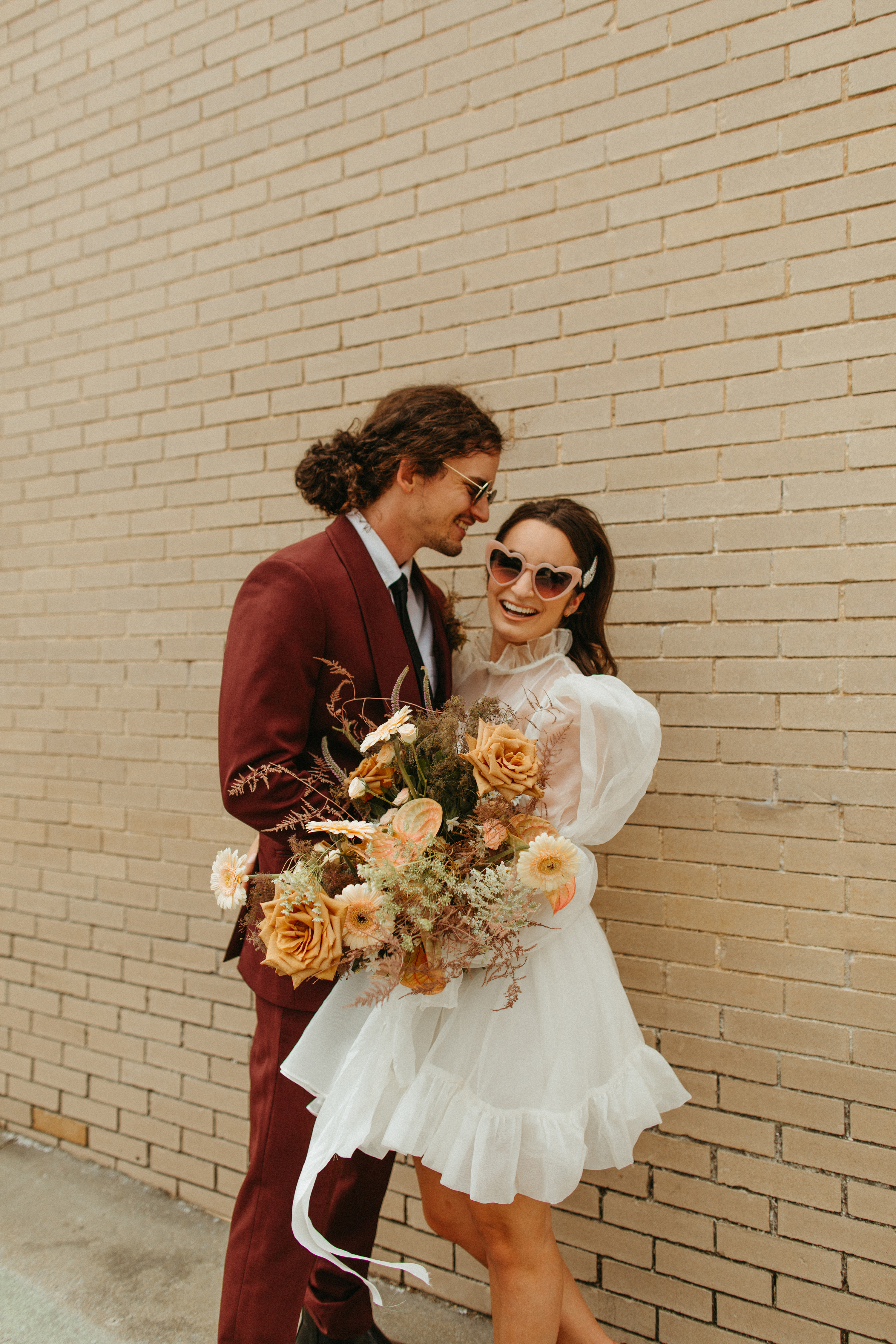 bride and groom with retro bridal bouquet and heart bridal sunglasses