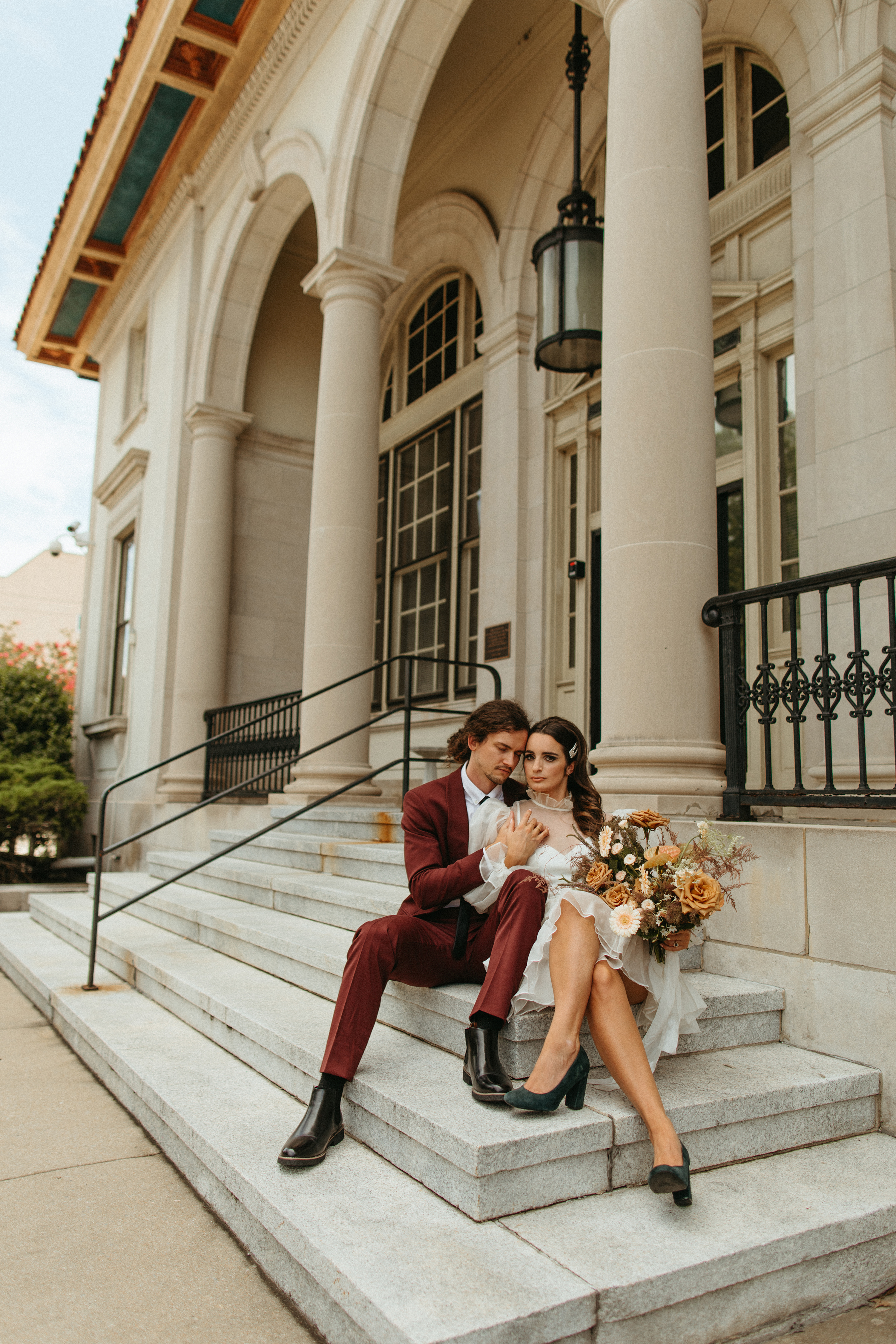 bride and groom sitting on the steps at city hall