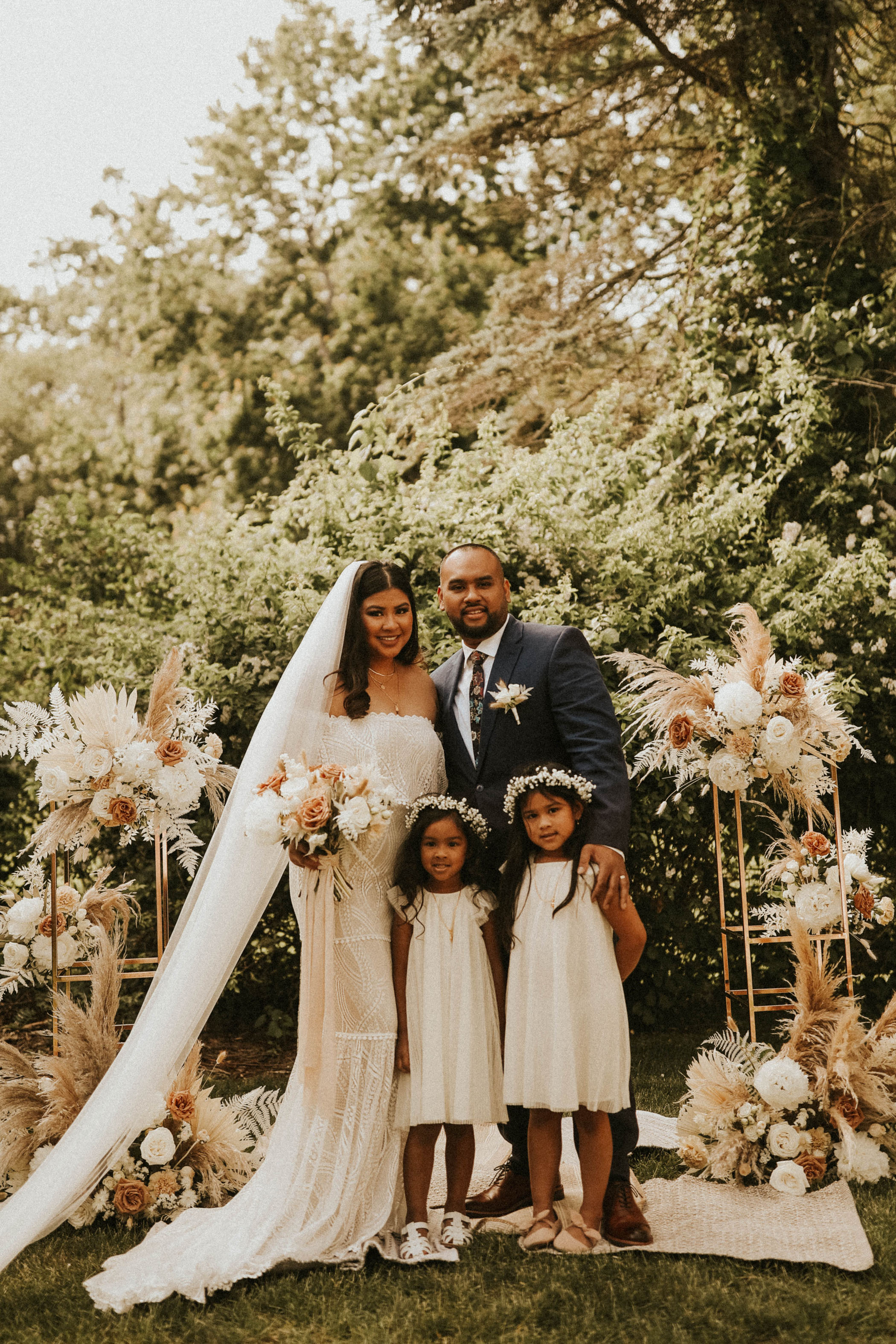 New husband and wife hugging their two daughters on their wedding day