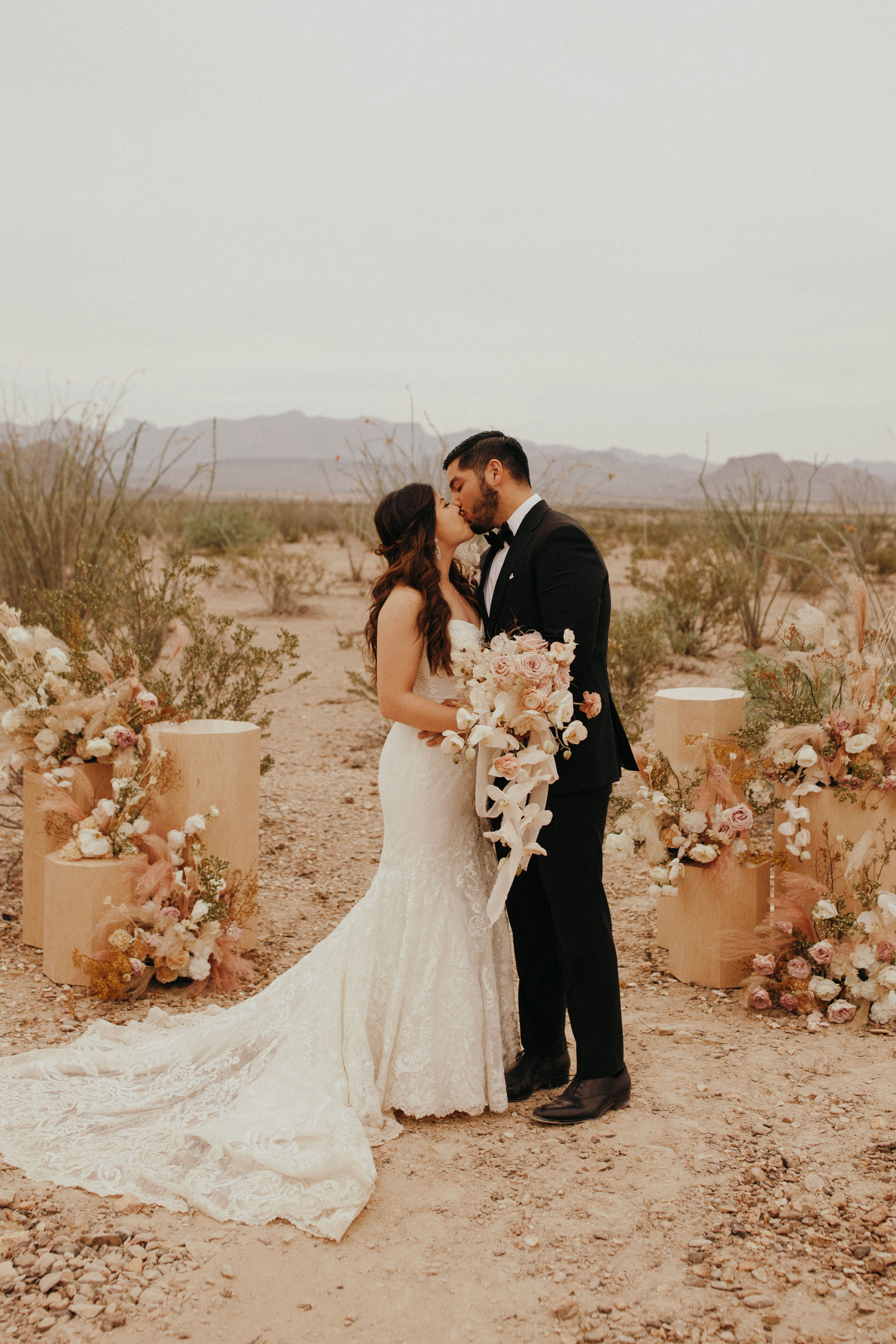 Husband and wife posing in front of a desert landscape