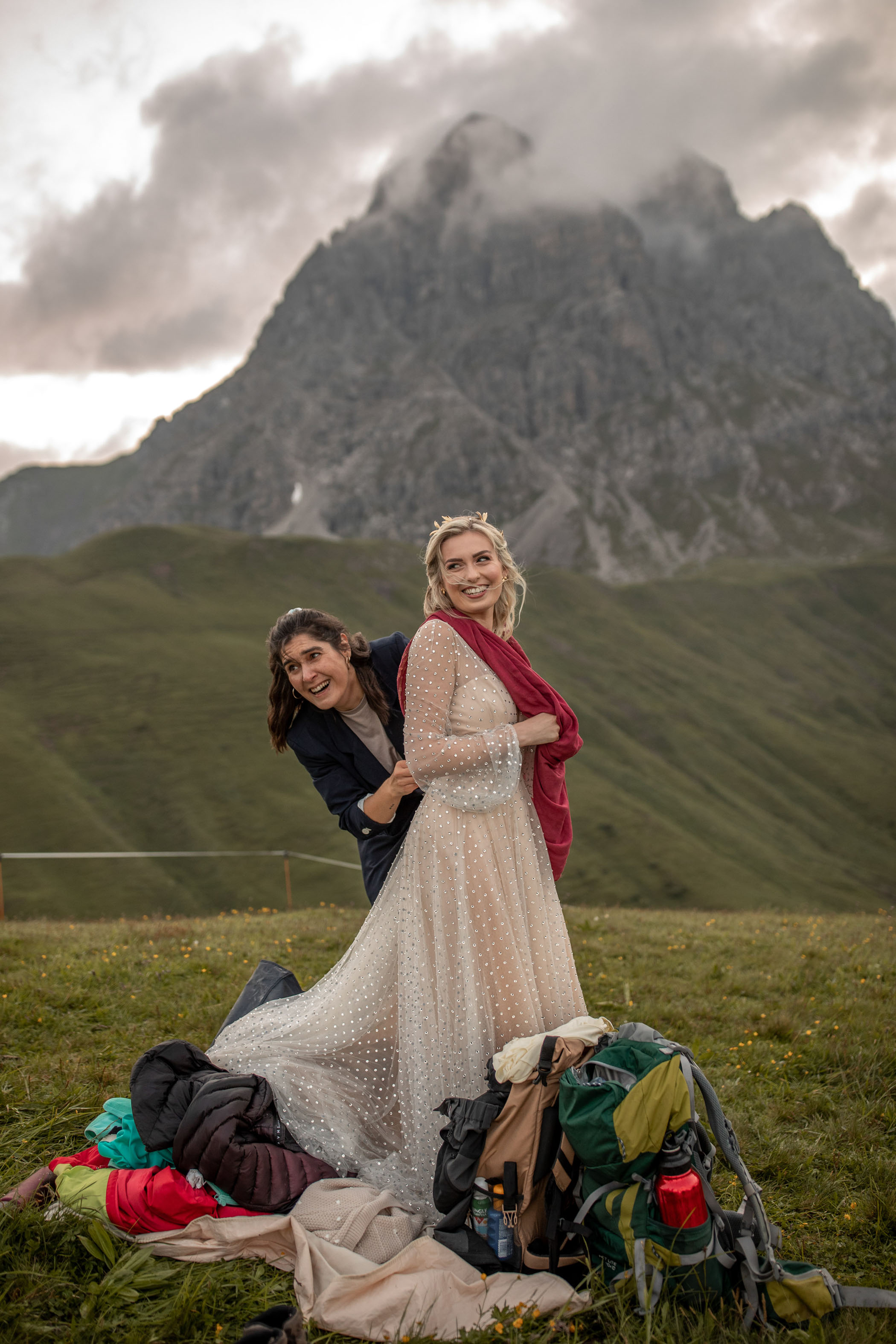Bride smiling being helped into her wedding dress after hiking up to her venue