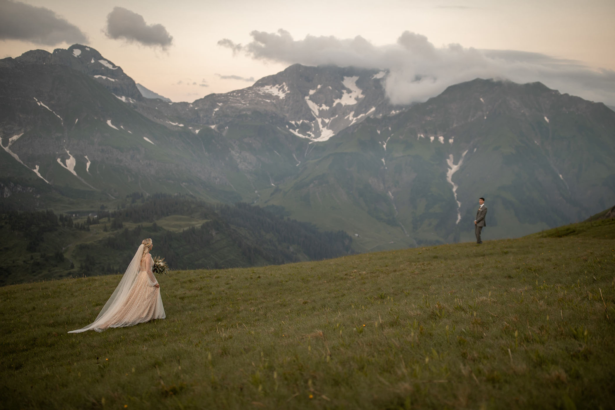 Bride in gold dress walks up to her groom on a mountain top