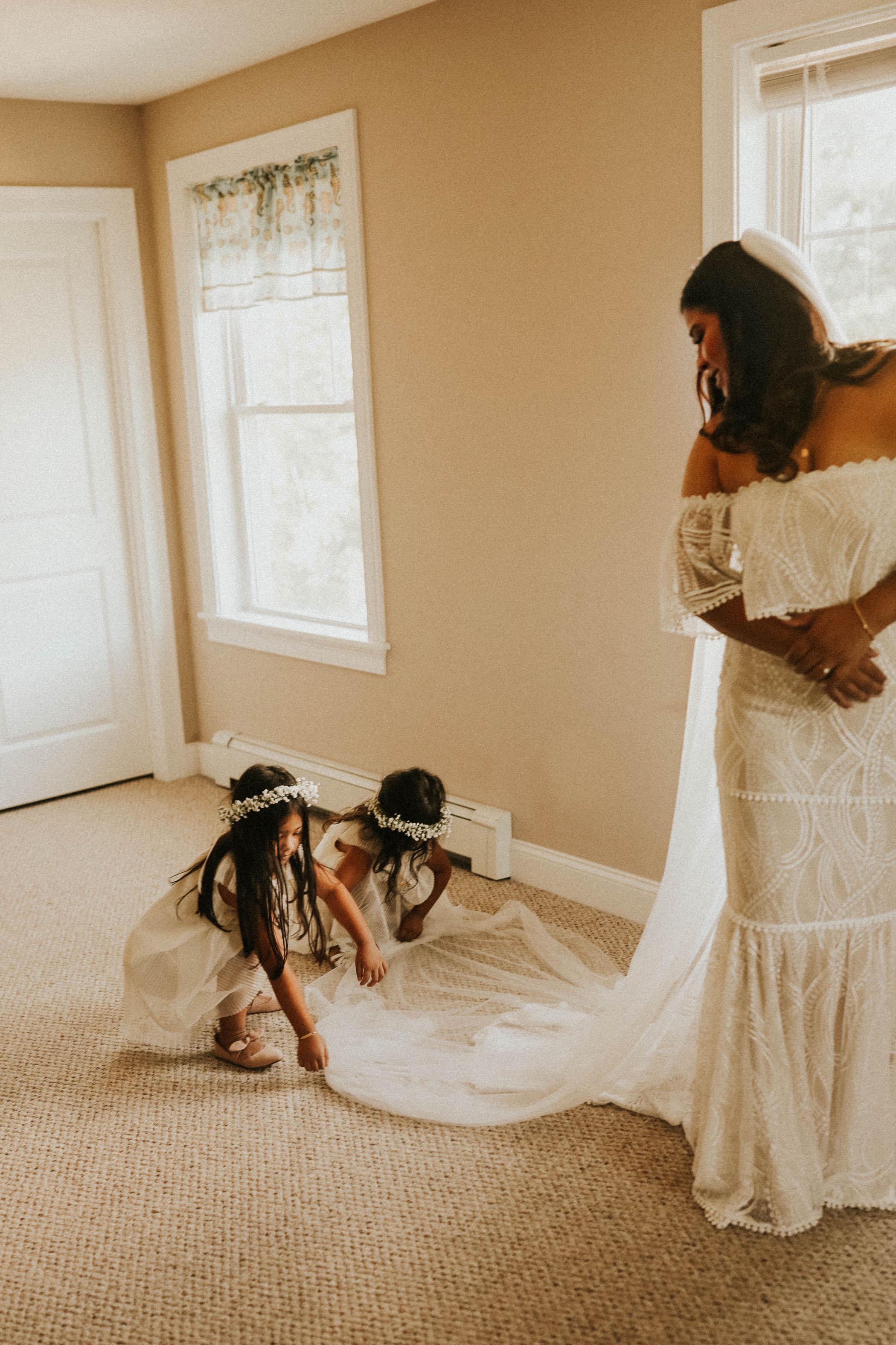 Two little girls fixing their mom's wedding dress train