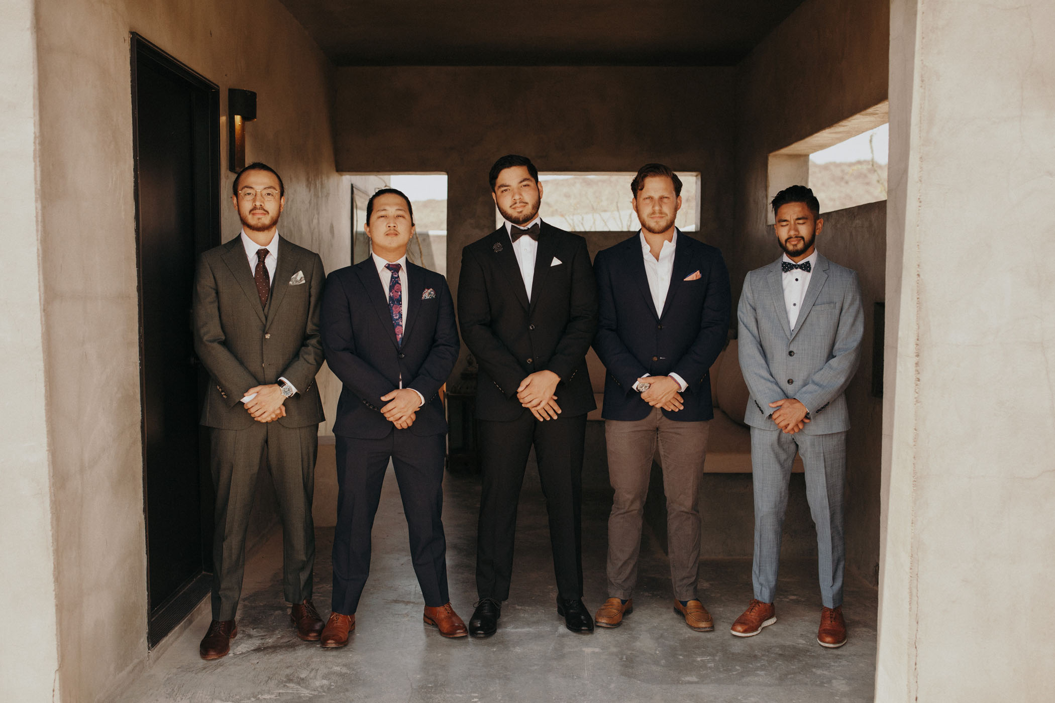 groomsmen in mismatched colored suits
