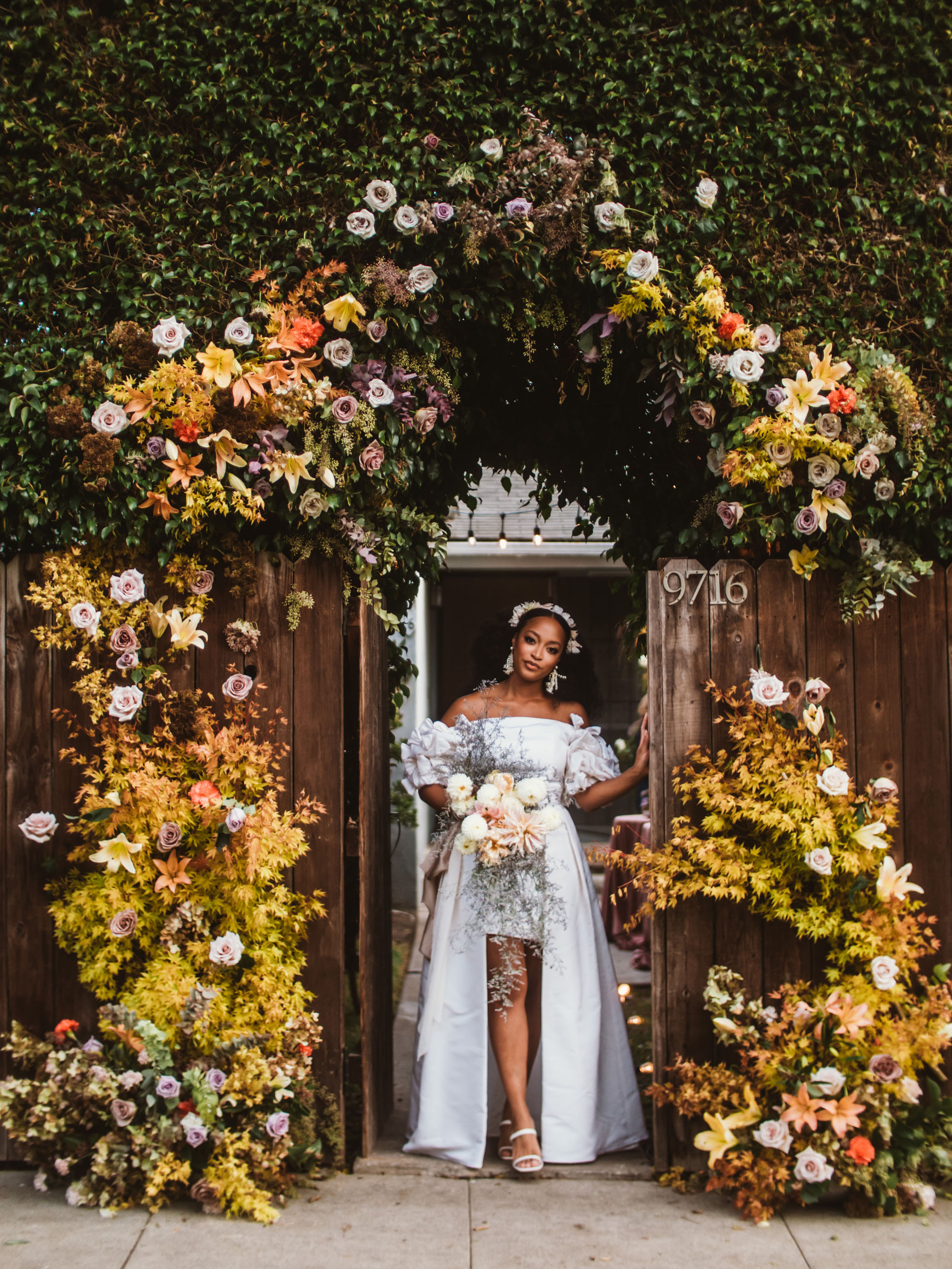 Bride in a high-low wedding gown with off the shoulder sleeves and a floral headpiece