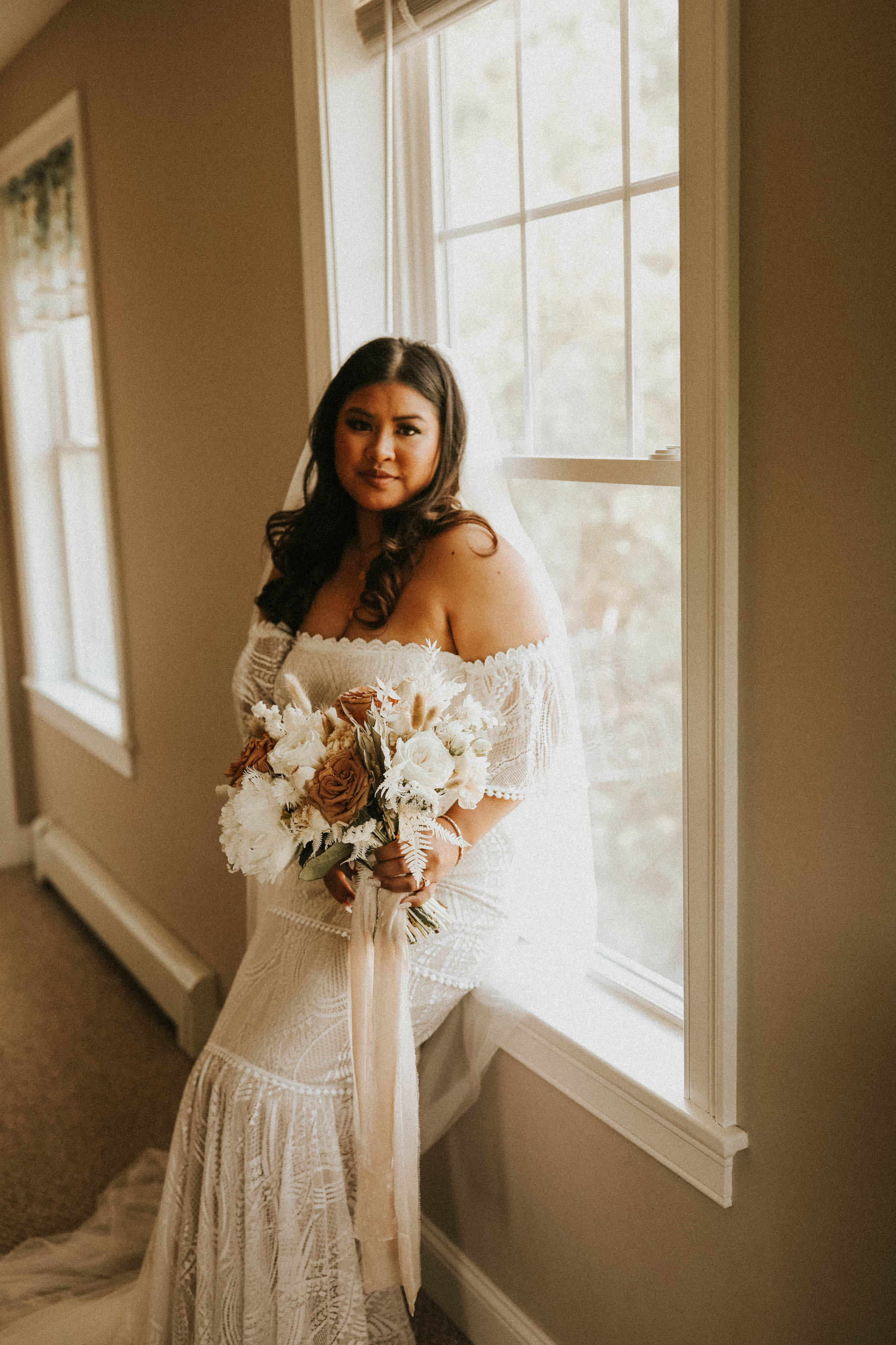 Bride in an off the shoulder boho wedding gown at home