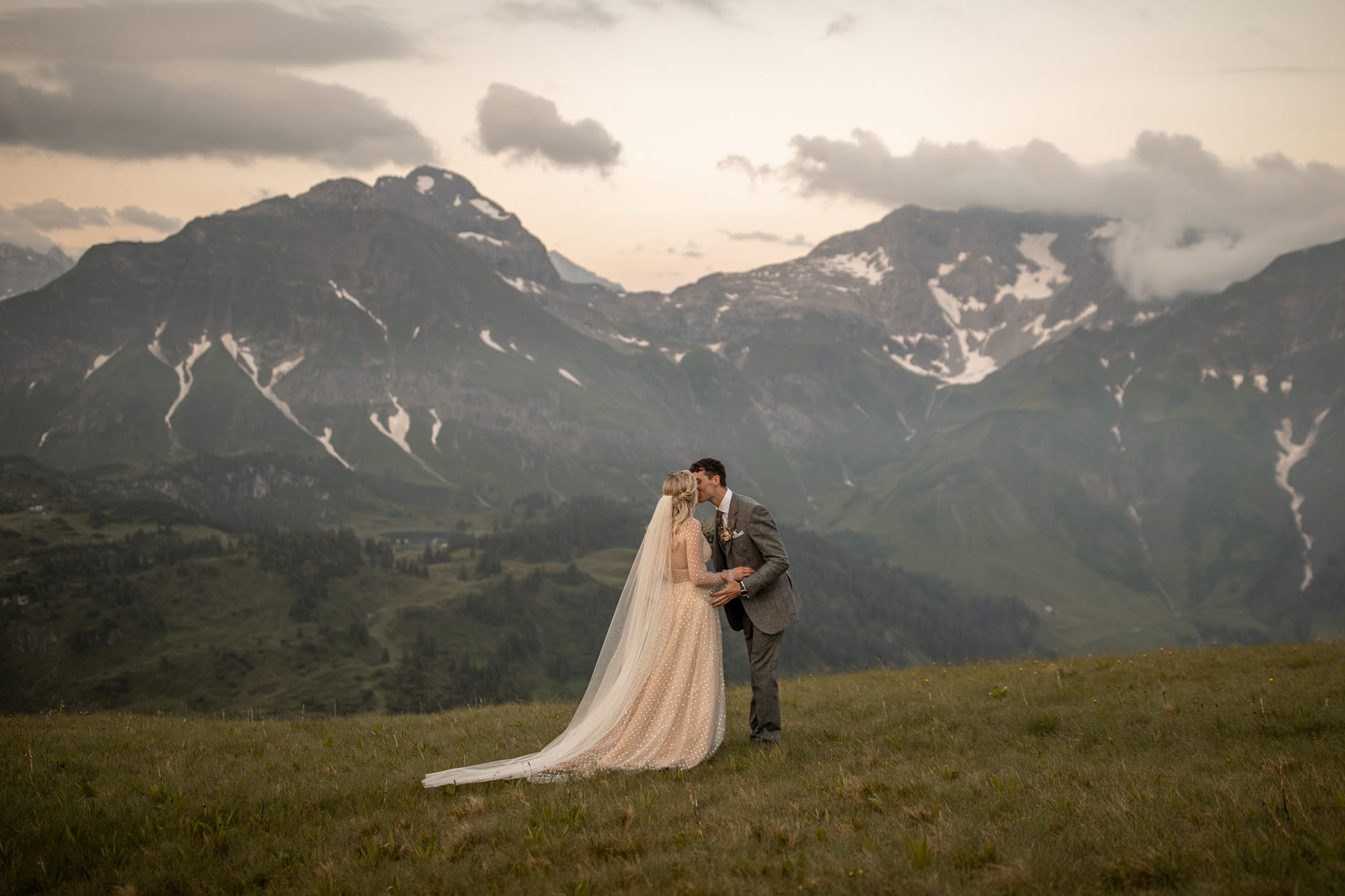 Bride in gold dress kisses her groom in front of the mountains