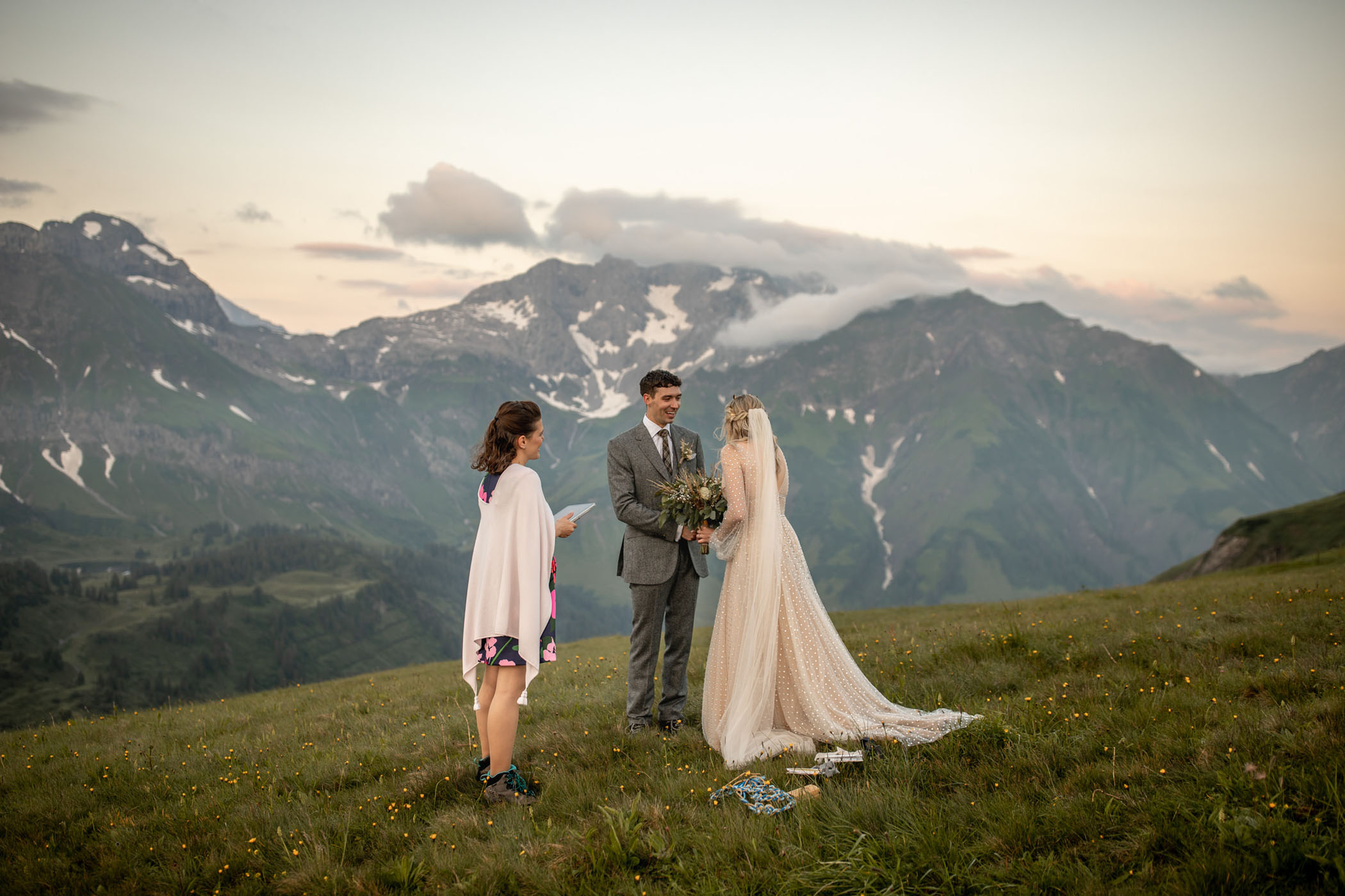 Bride, groom, and minister in front of mountains