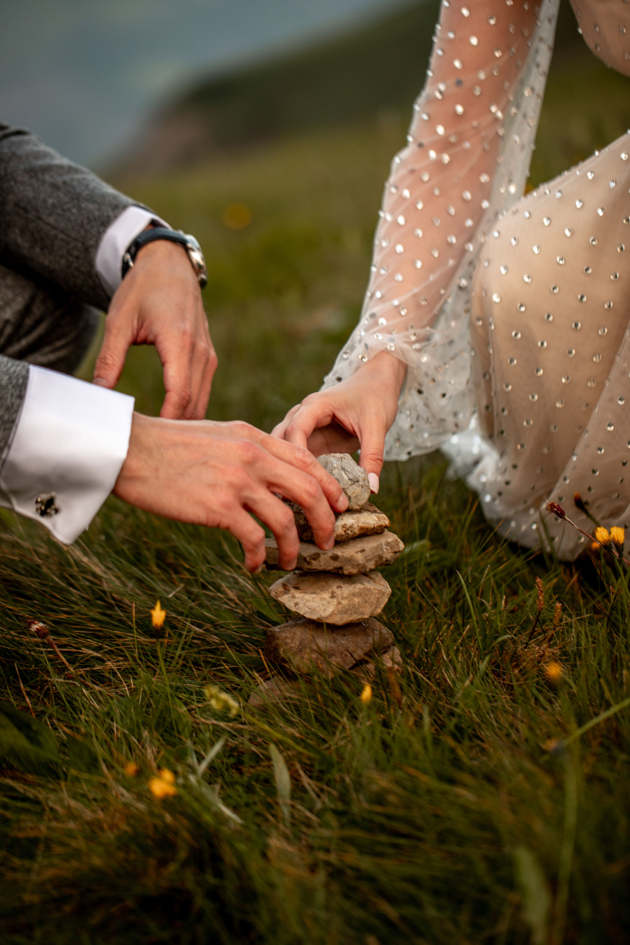 Couple holding hands while stacking rocks