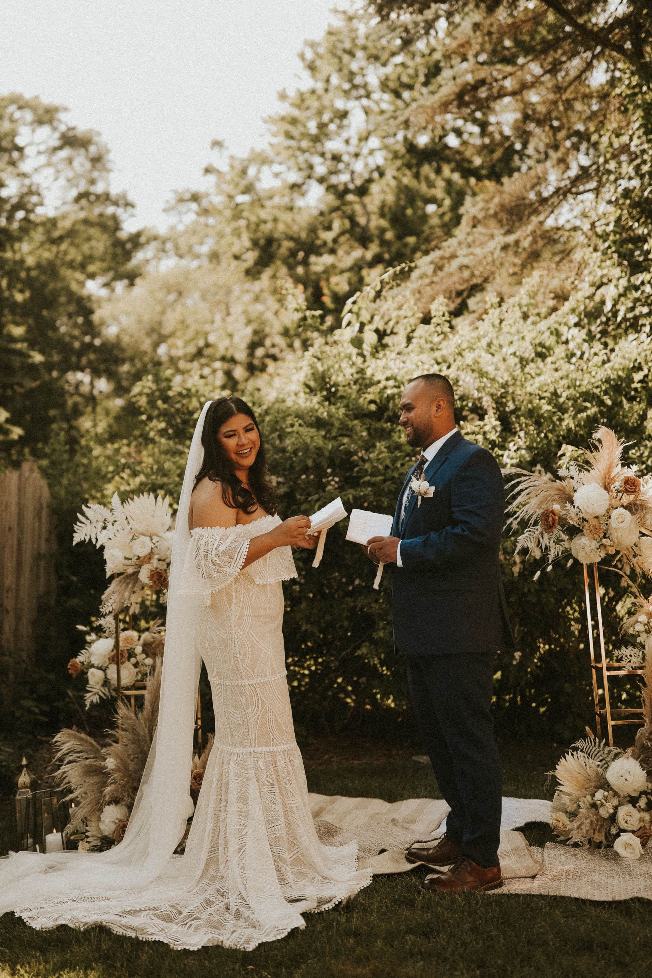 Husband and wife say their vows in their backyard boho wedding ceremony