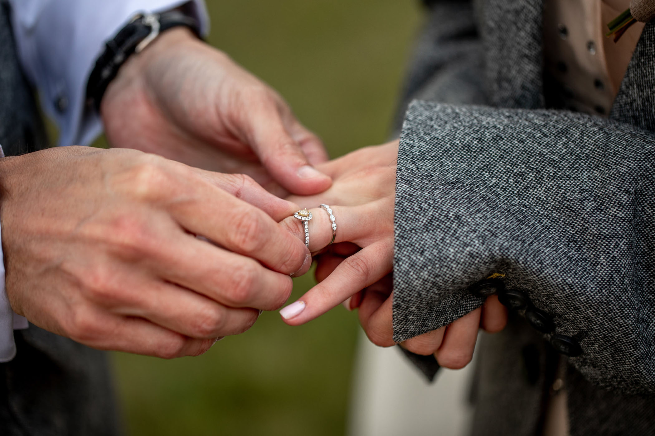 Groom places a pear wedding ring on his wife's finger
