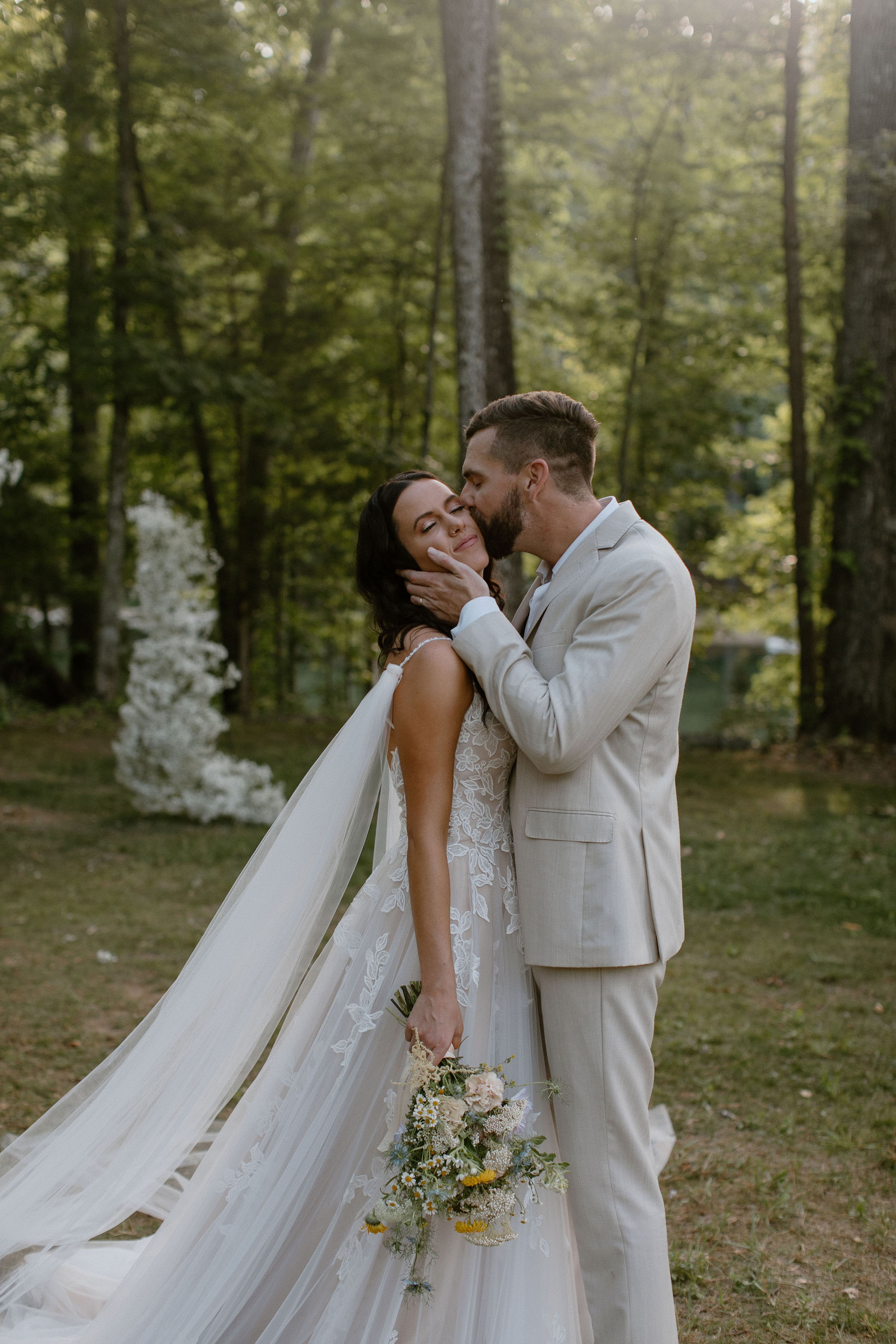 Groom kisses his bride on the cheek in their forest wedding